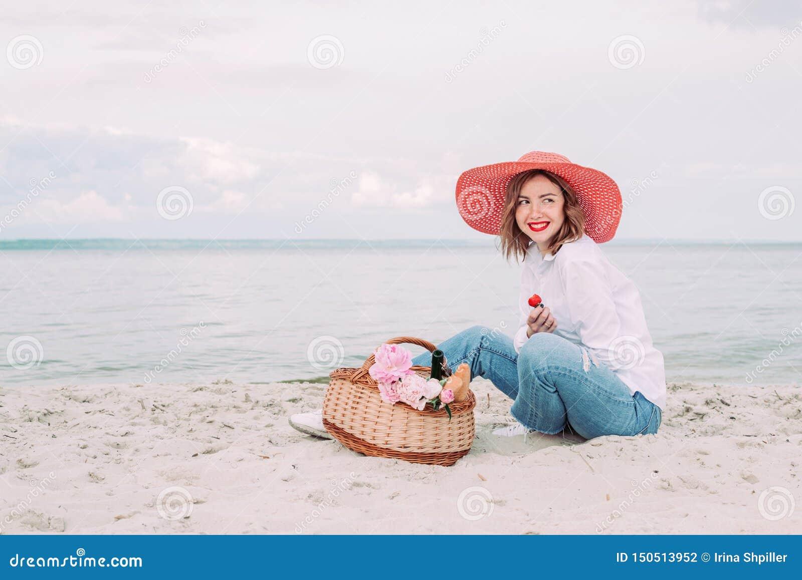 Красивая девушка в красной шляпе с корзиной пикника на портовом районе лета