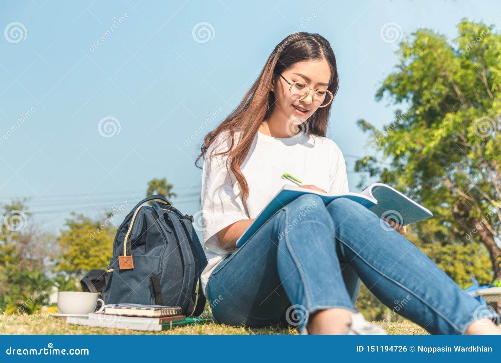 Красивая девушка в лесе осени читая книгу покрытую с теплым одеялом женщина сидит около дерева в лесе и владениях лета