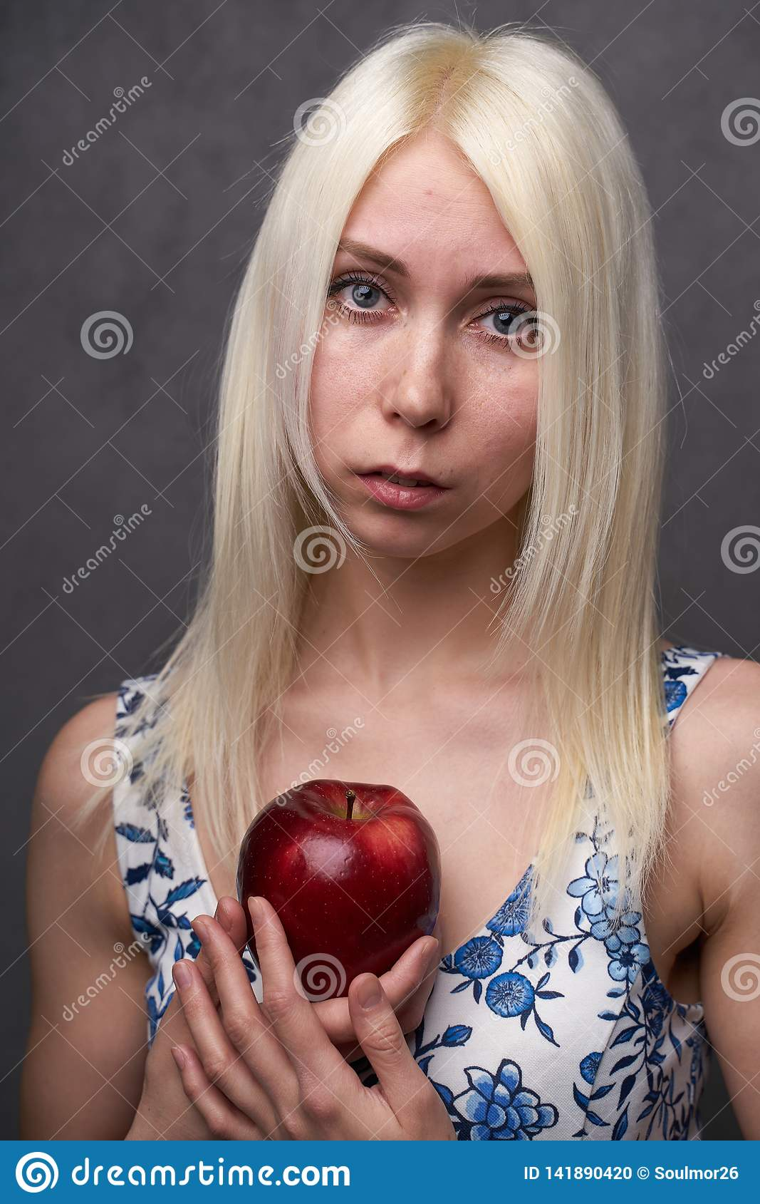Красивая девушка в модном платье с яблоком
