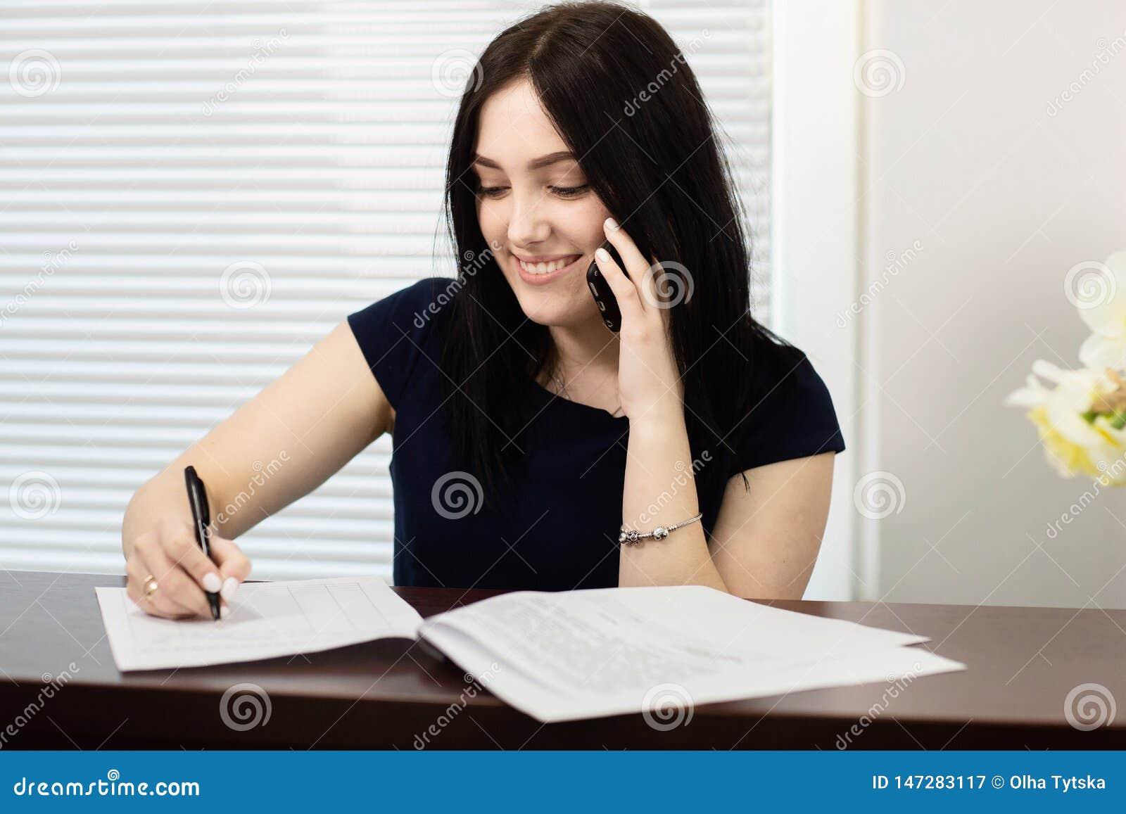 Красивая девушка на приемной отвечая звонку в зубоврачебном офисе