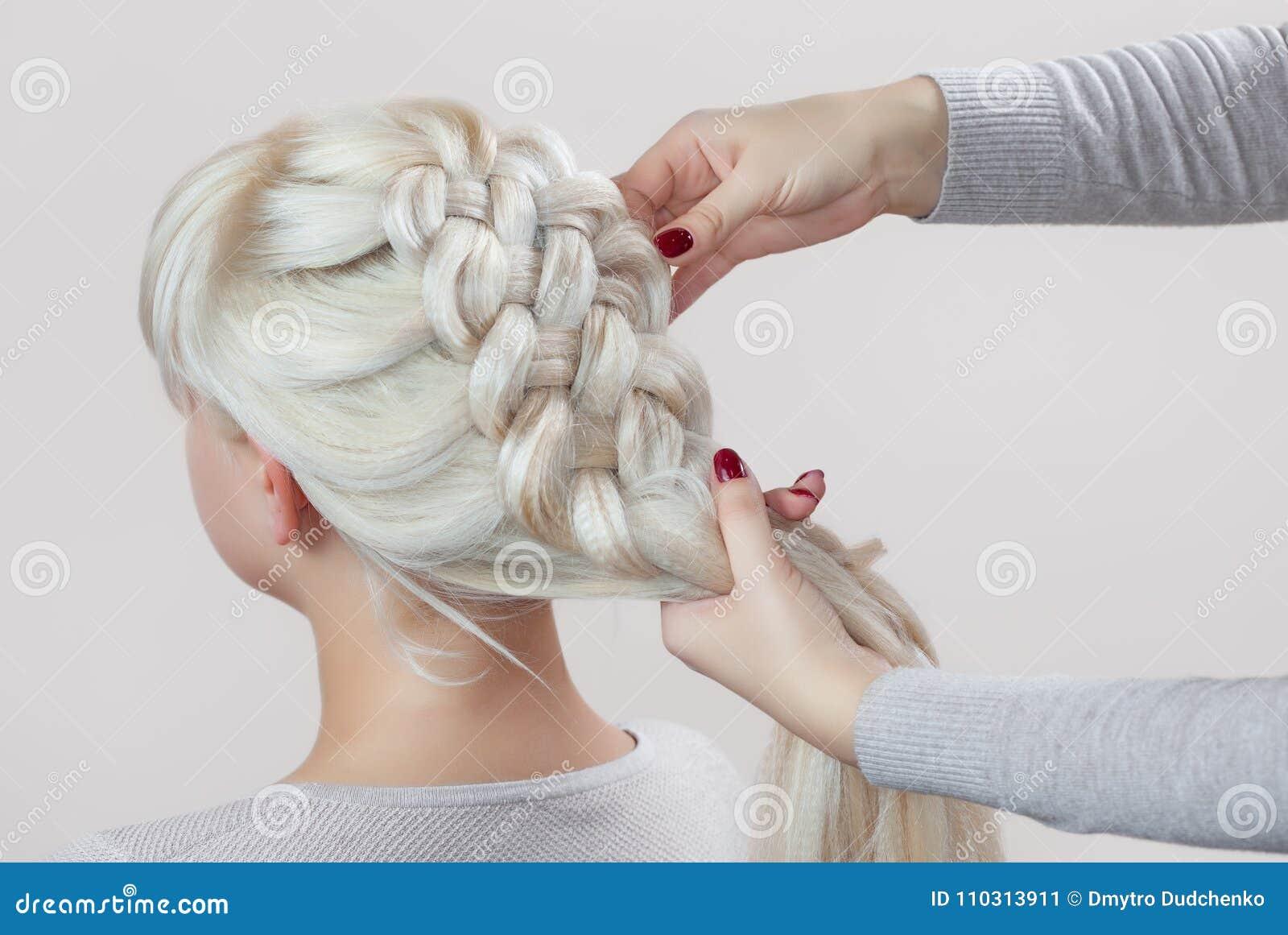 Красивая девушка с белокурыми волосами, парикмахер соткет конец-вверх оплетки