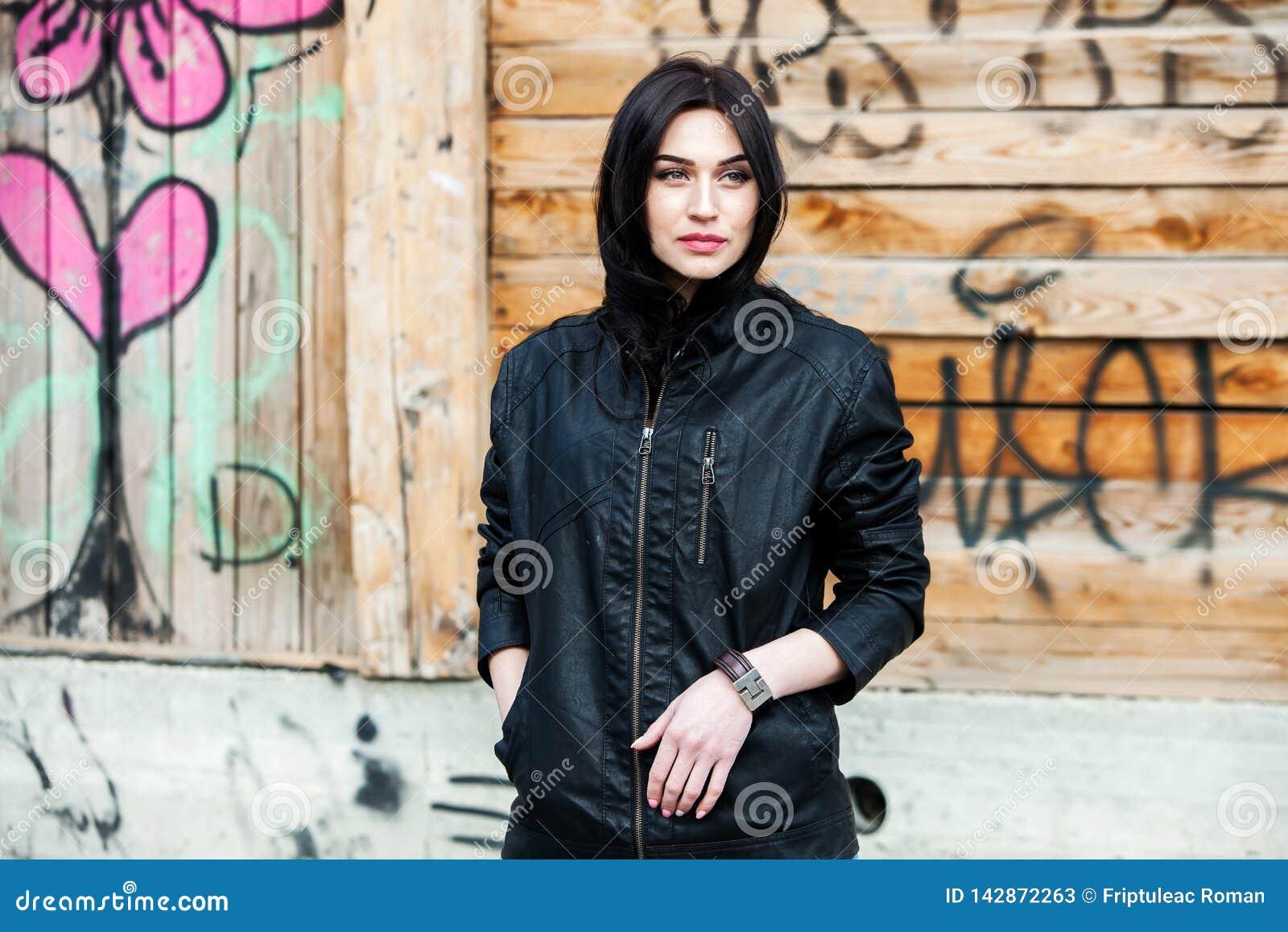 Красивая девушка с волнистыми волосами в черной кожаной куртке Портрет милой молодой женщины дела напольной
