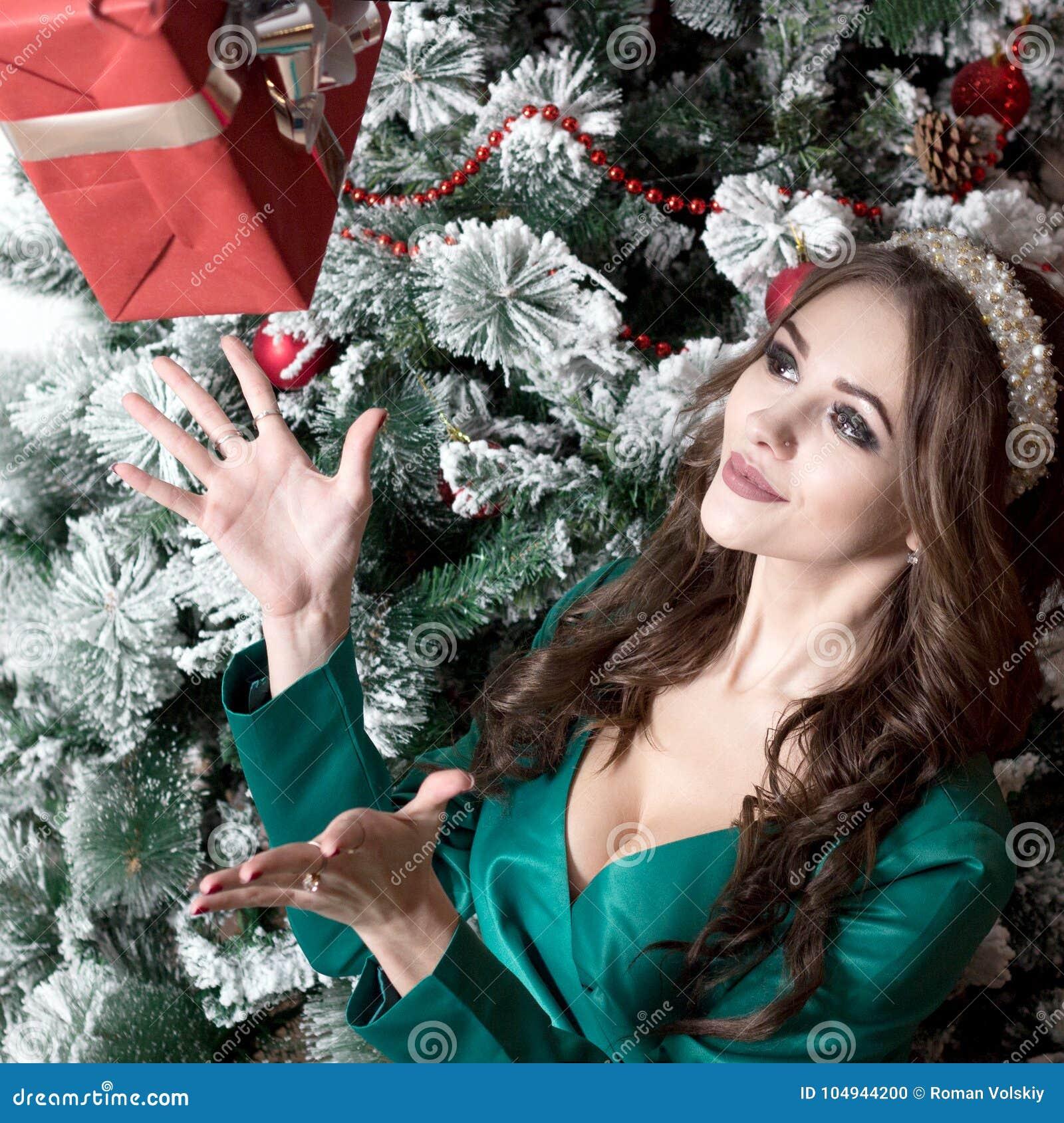 bd2aeadca8e6 Красивая девушка с длинными волосами в зеленом платье с вырезом на ее  комоде улавливает красную коробку