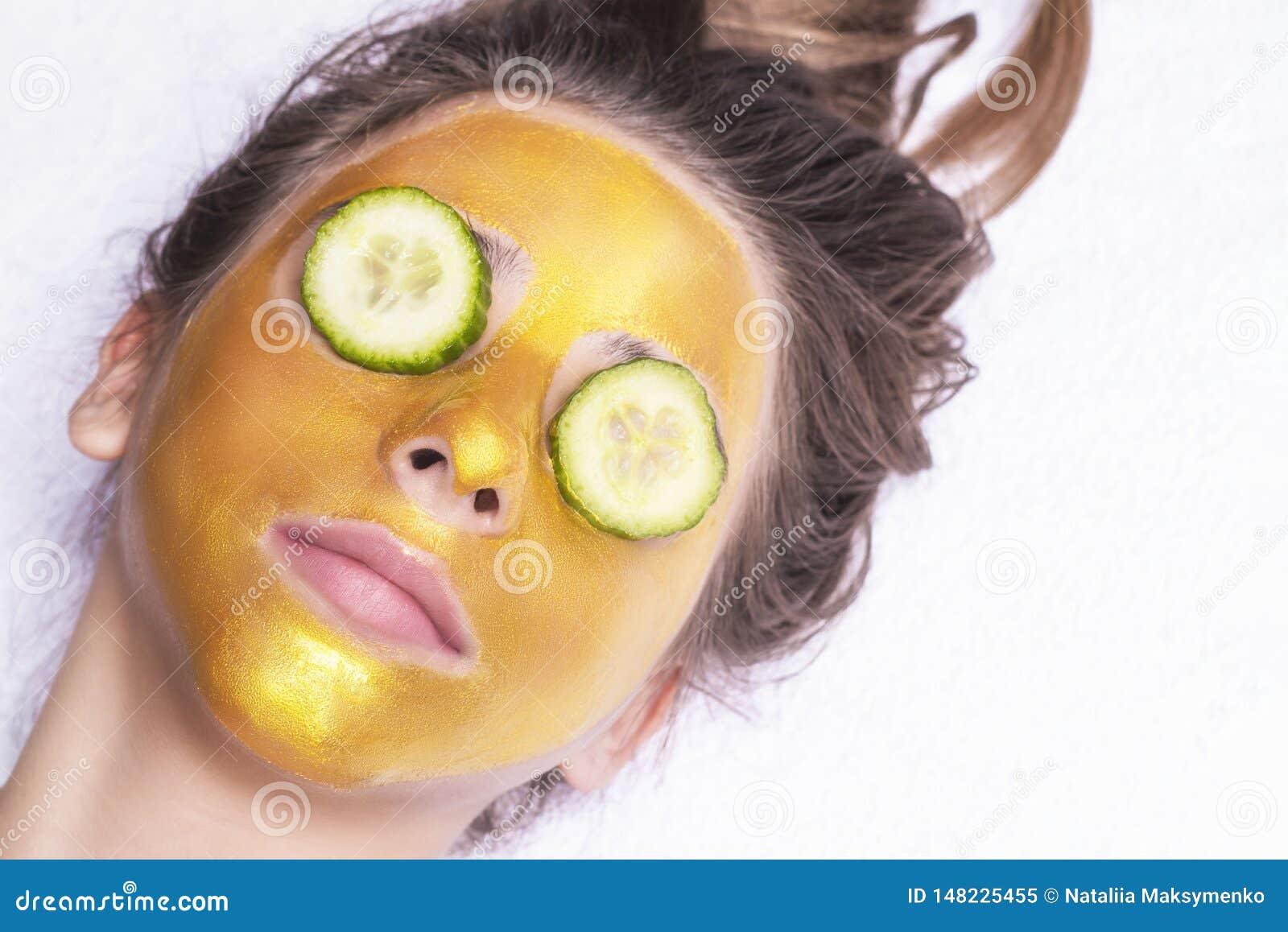 Красивая девушка с косметической маской на стороне золотого цвета : r Маска золота женщины Красивая модель извлекая