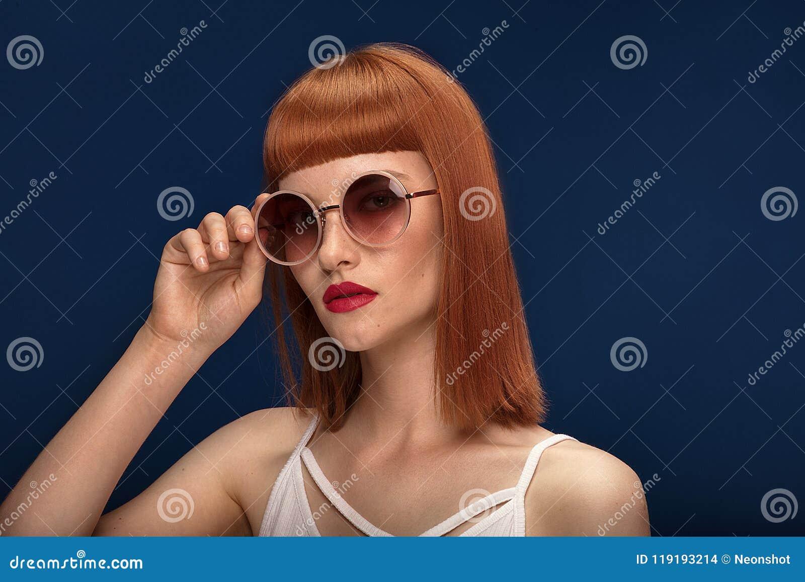 Красивая девушка redhead в солнечных очках на голубой предпосылке