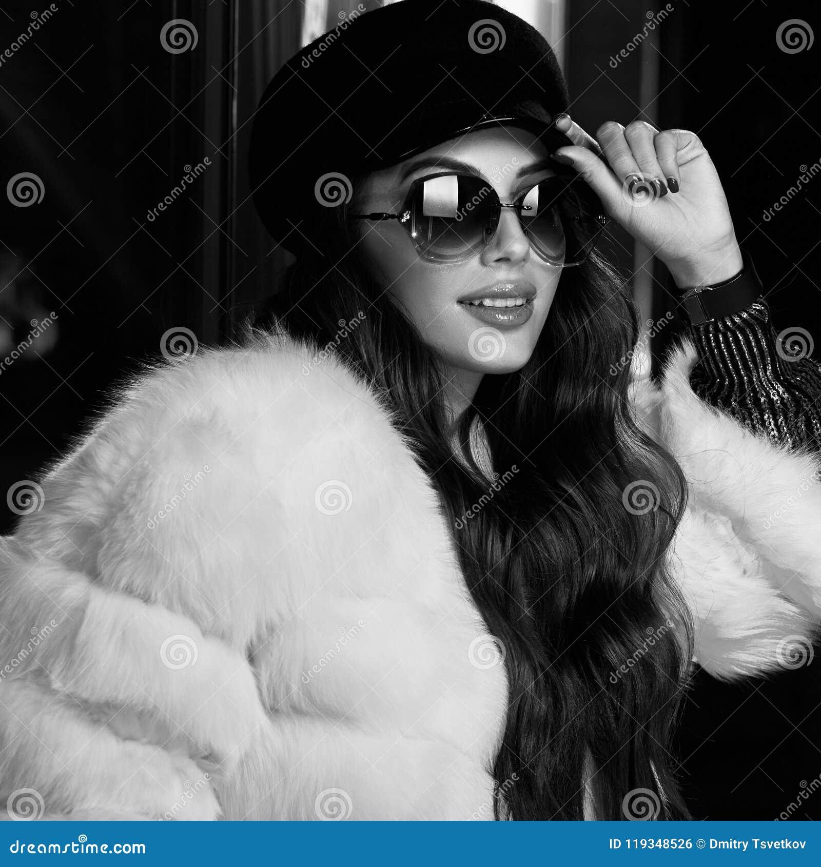 Красивая длинная с волосами женщина в крышке, солнечных очках и белом coa меха