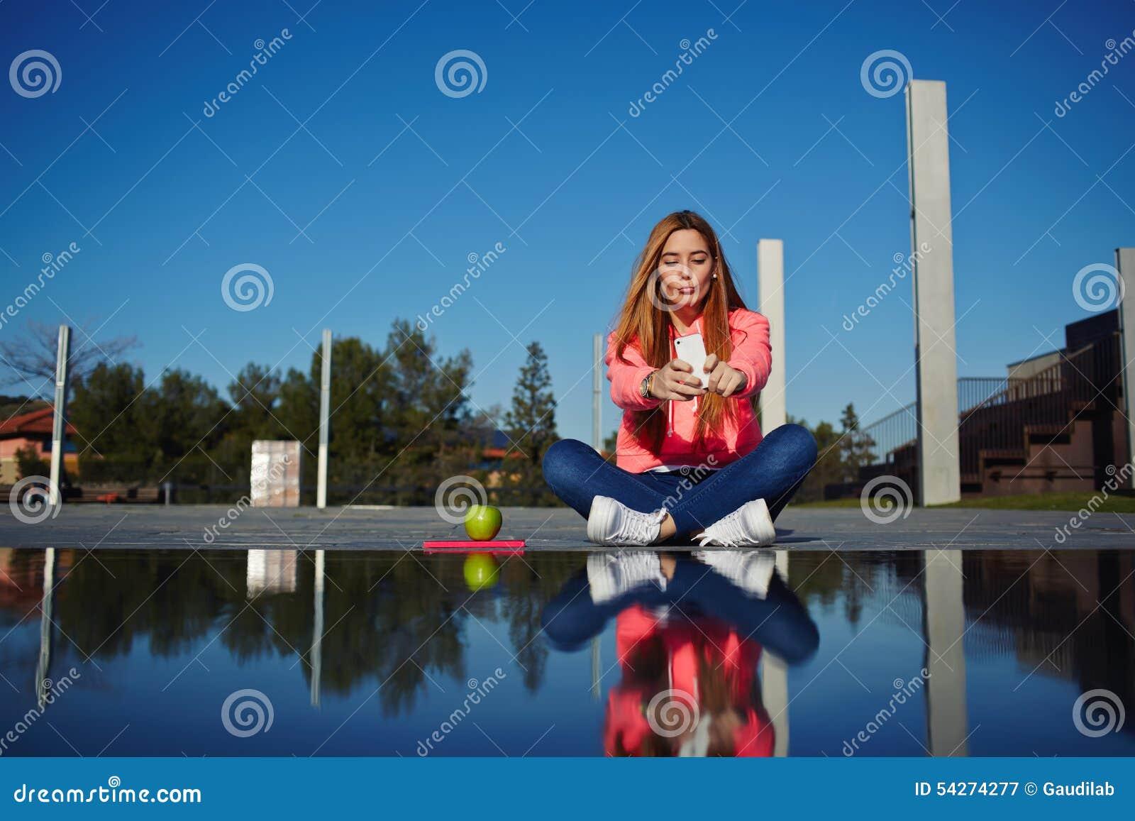 Красивая девушка битника фотографирует ее собственная личность с сотовым телефоном