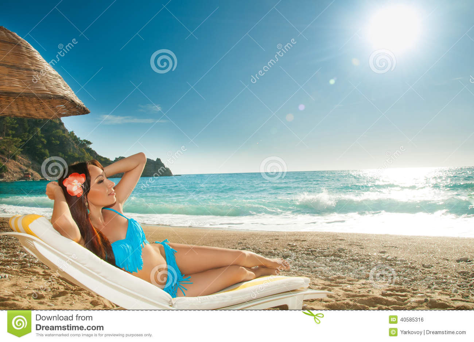 Красивая девушка брюнет загорая на sunbed на море