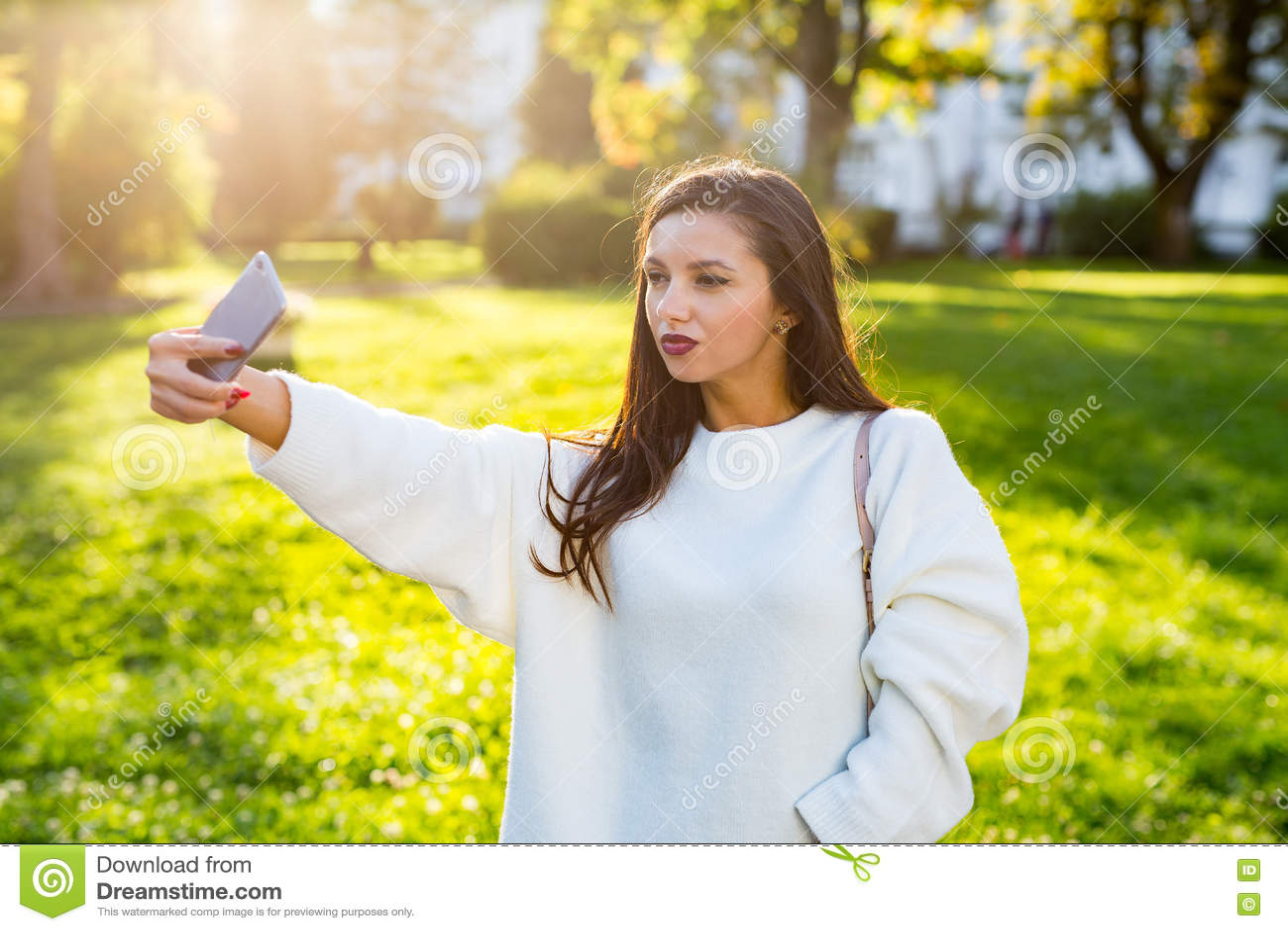 Красивая девушка брюнет принимая автопортрет в парке на заход солнца