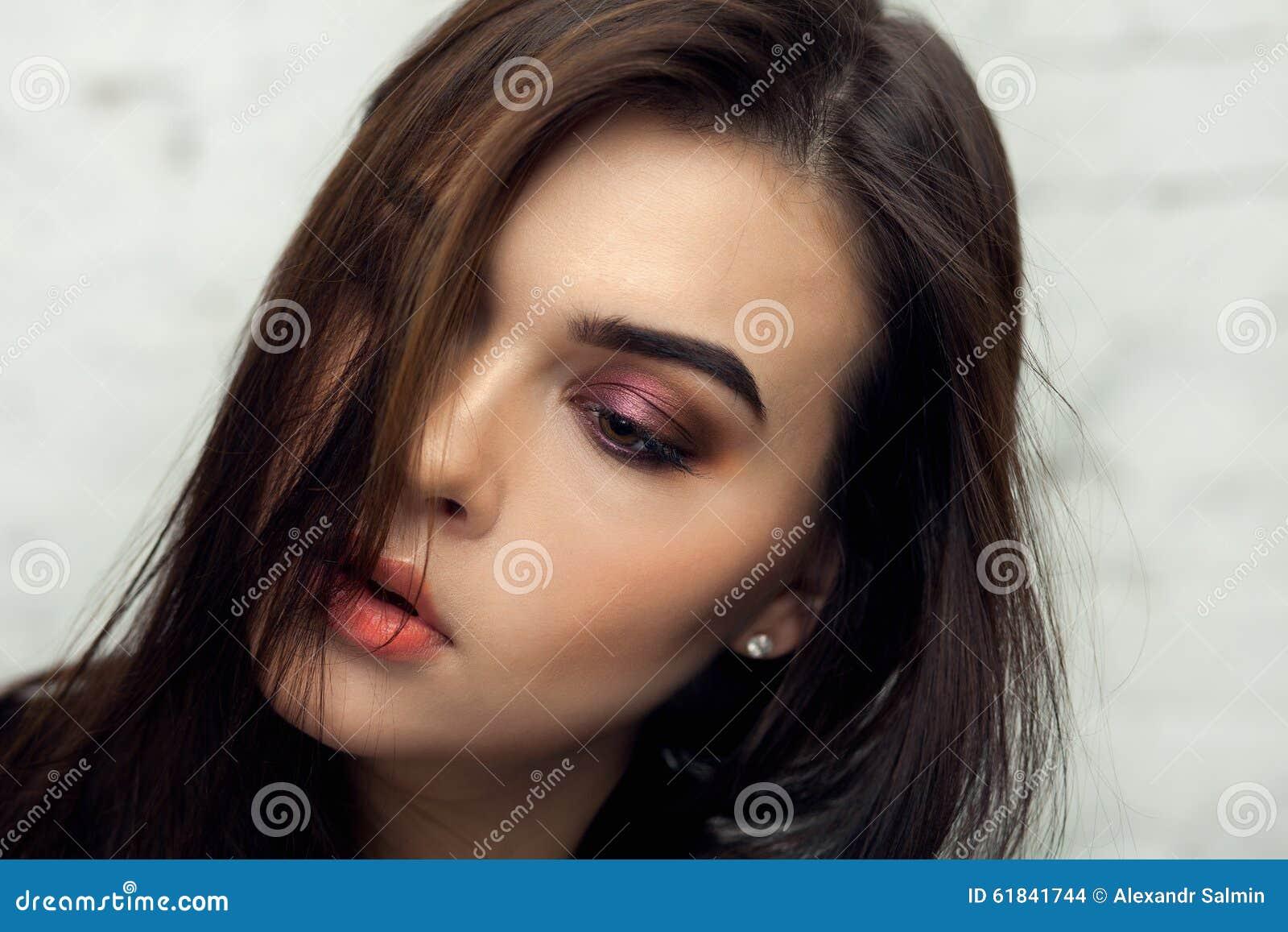 Красивая девушка брюнет с кабелем завитым волосами