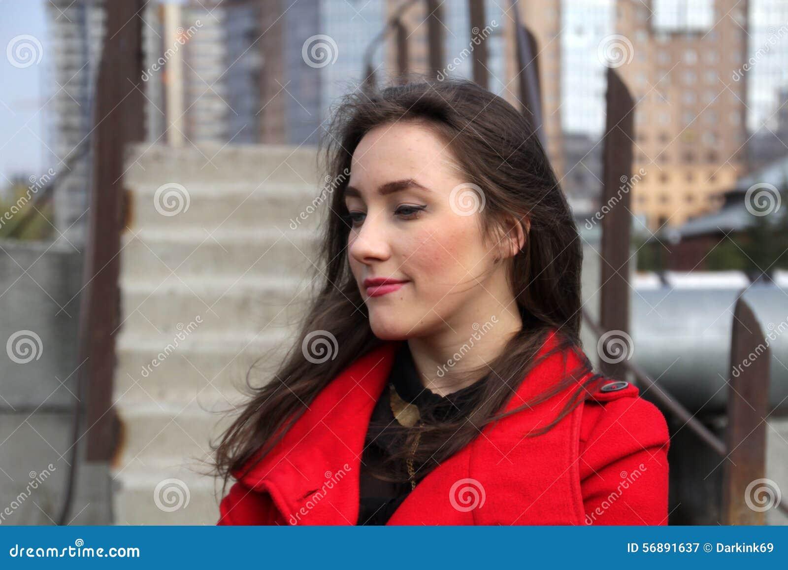 Красивая девушка в красном пальто на предпосылке лестниц