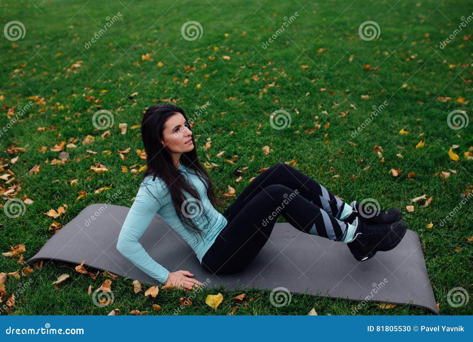 Красивая девушка делает тренировки с прессой на траве