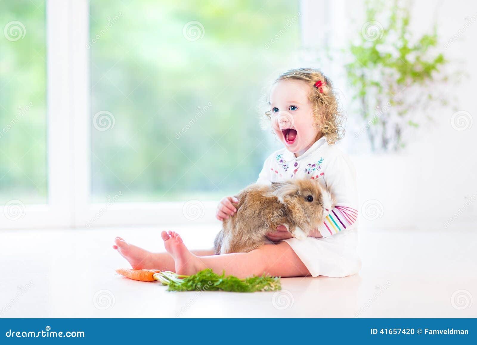 Красивая девушка малыша с вьющиеся волосы с реальным зайчиком