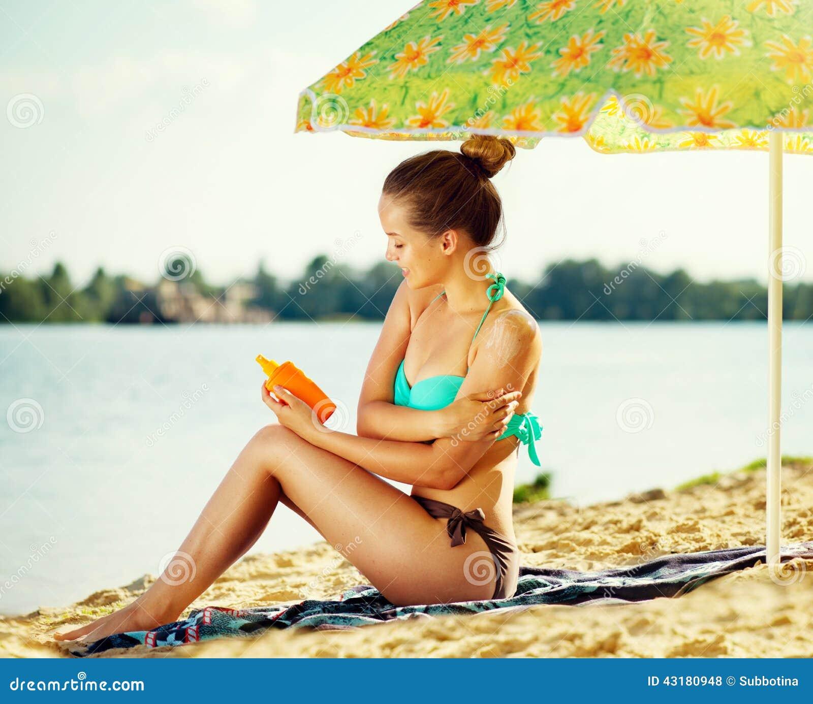 Красивая девушка прикладывая сливк suntan на ее коже