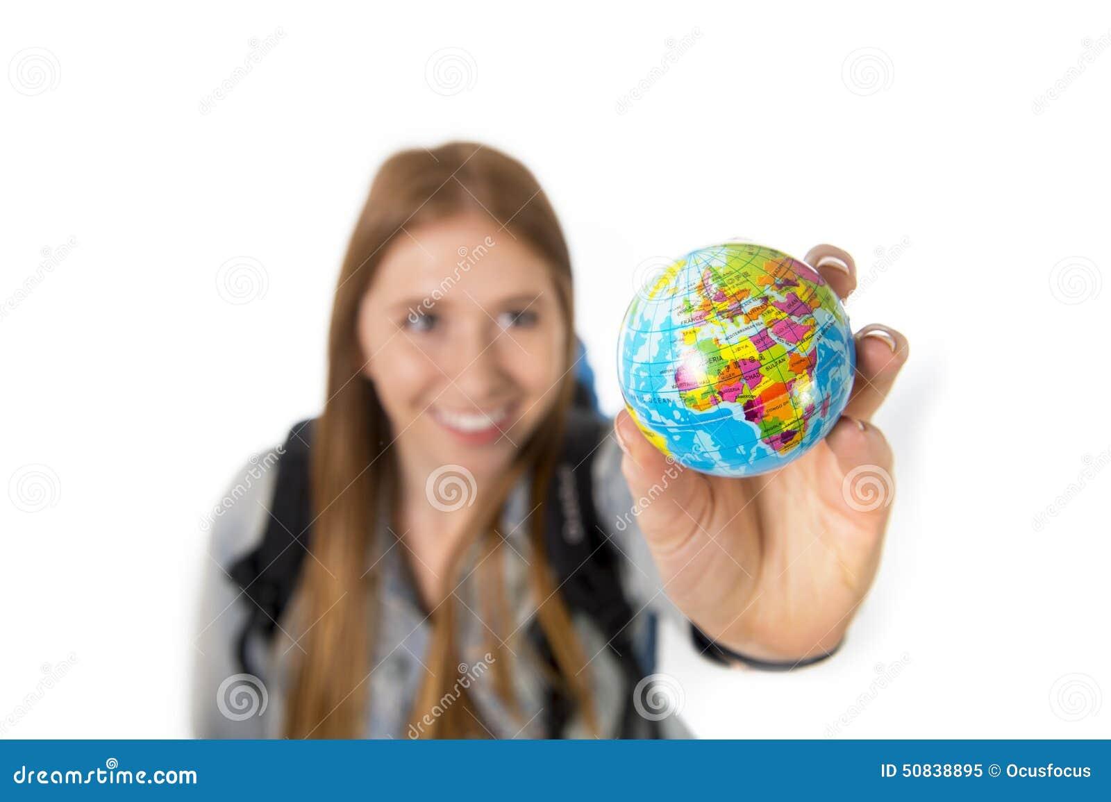 Красивая девушка студента держа меньший глобус мира в ее руке выбирая назначение праздников в концепции туризма перемещения