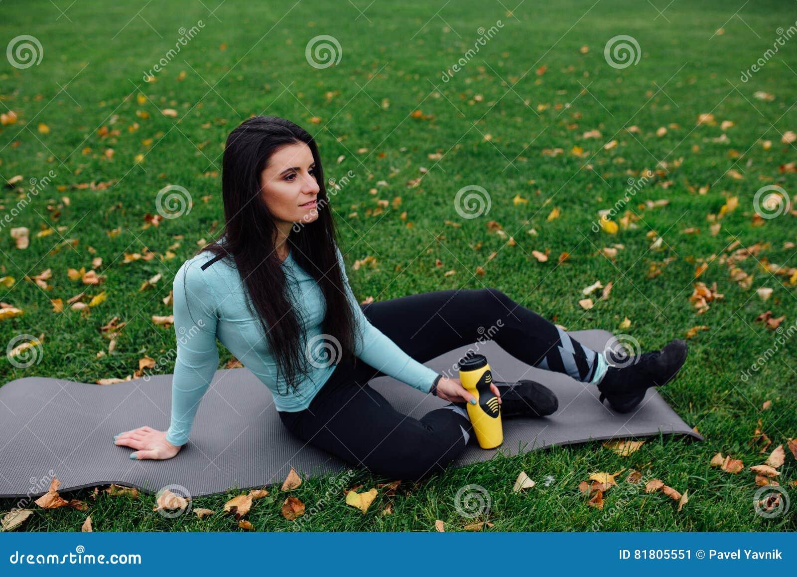 Красивая девушка с бутылкой воды в руку на траве