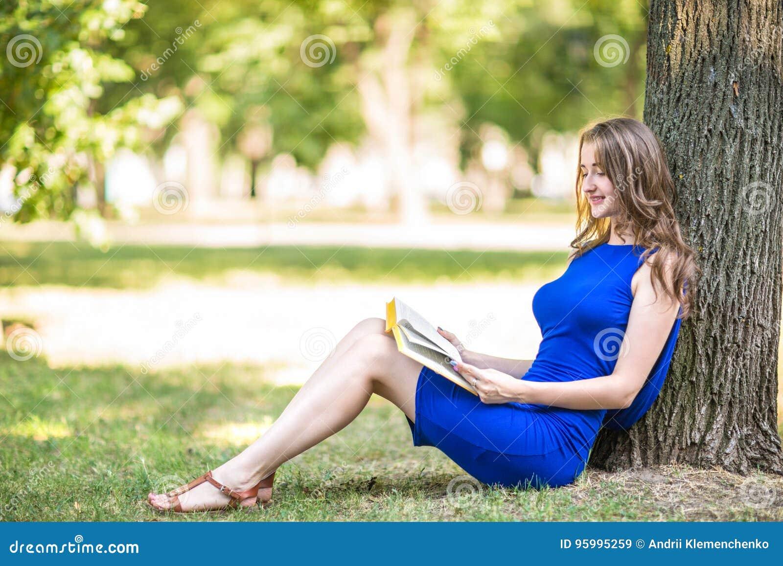 Красивая девушка с чудесными русыми волосами сидит около большого дерева и читает интересную книгу в зеленом парке