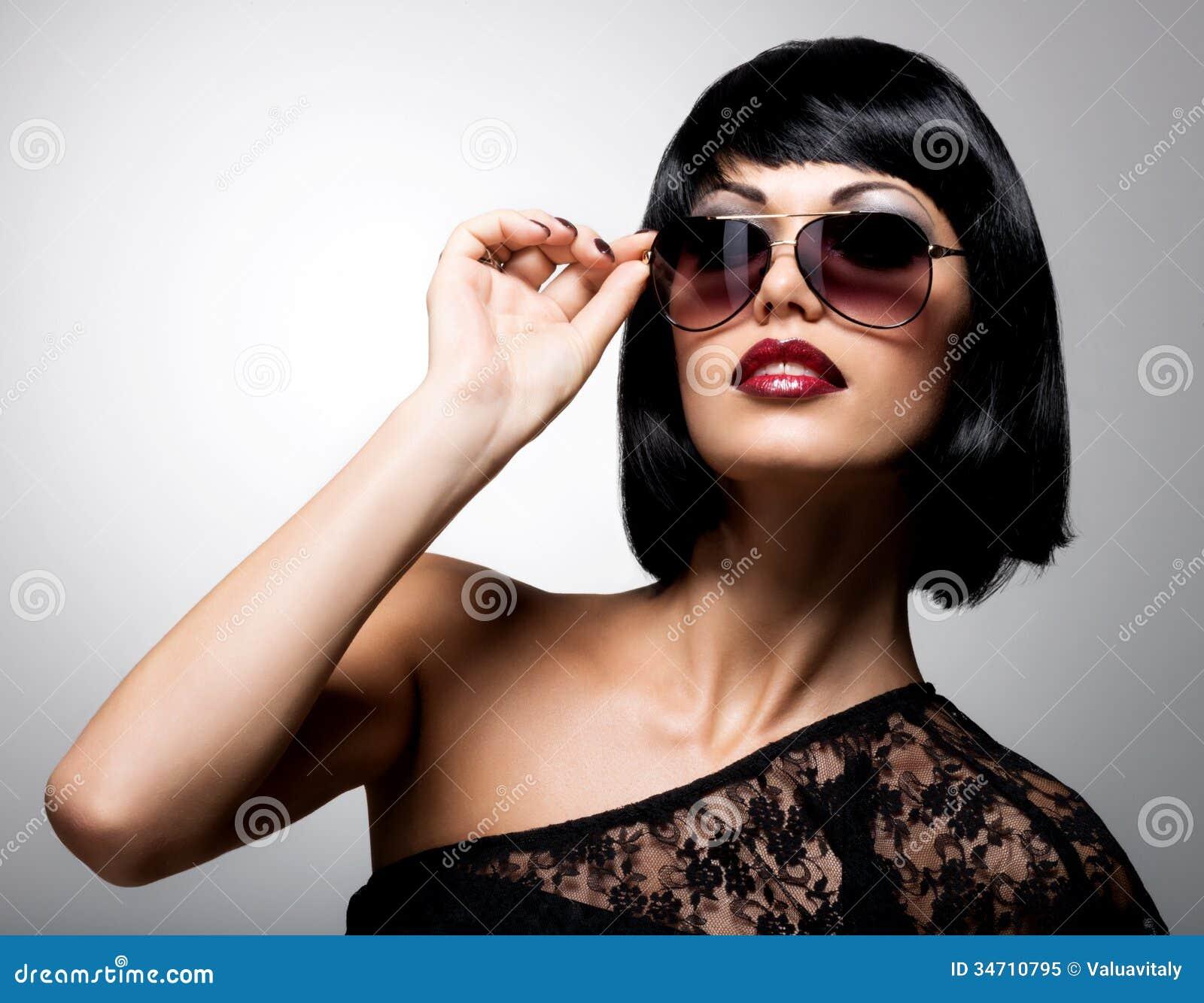 Красивая женщина брюнет с стилем причёсок съемки с красными солнечными очками