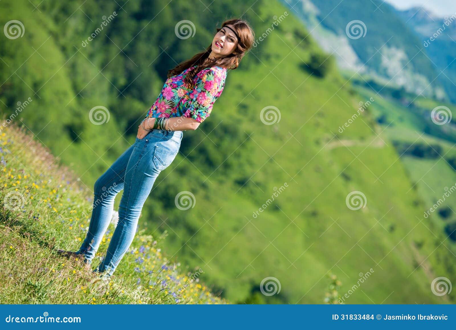 Красивая женщина в джинсах стоя на траве