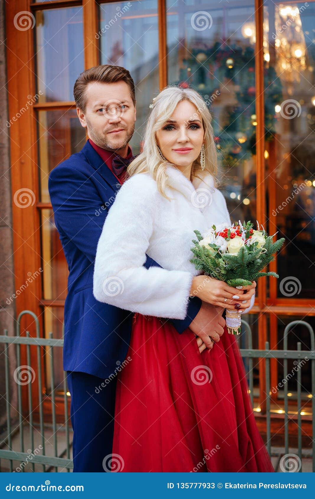 Красивая женщина в красном платье стоит с человеком, женихом и невеста, счастливыми новобрачными