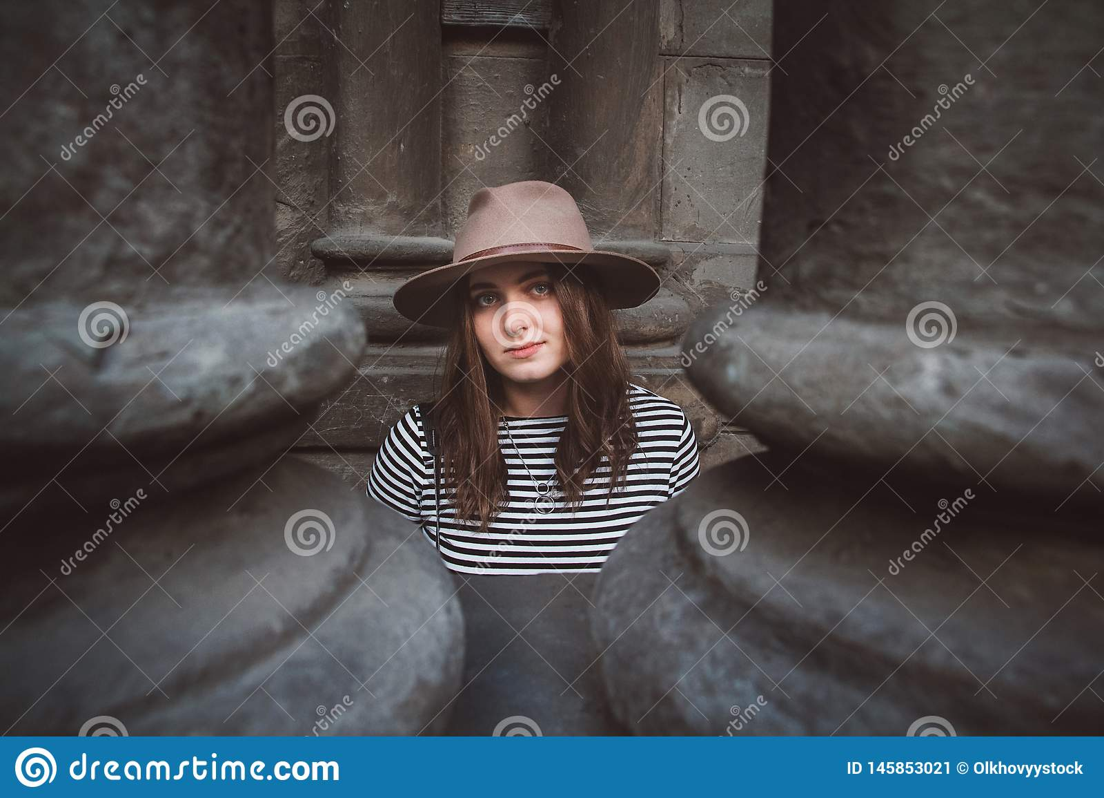 Красивая женщина в шляпе и striped рубашке смотря камеру Портрет конца-вверх