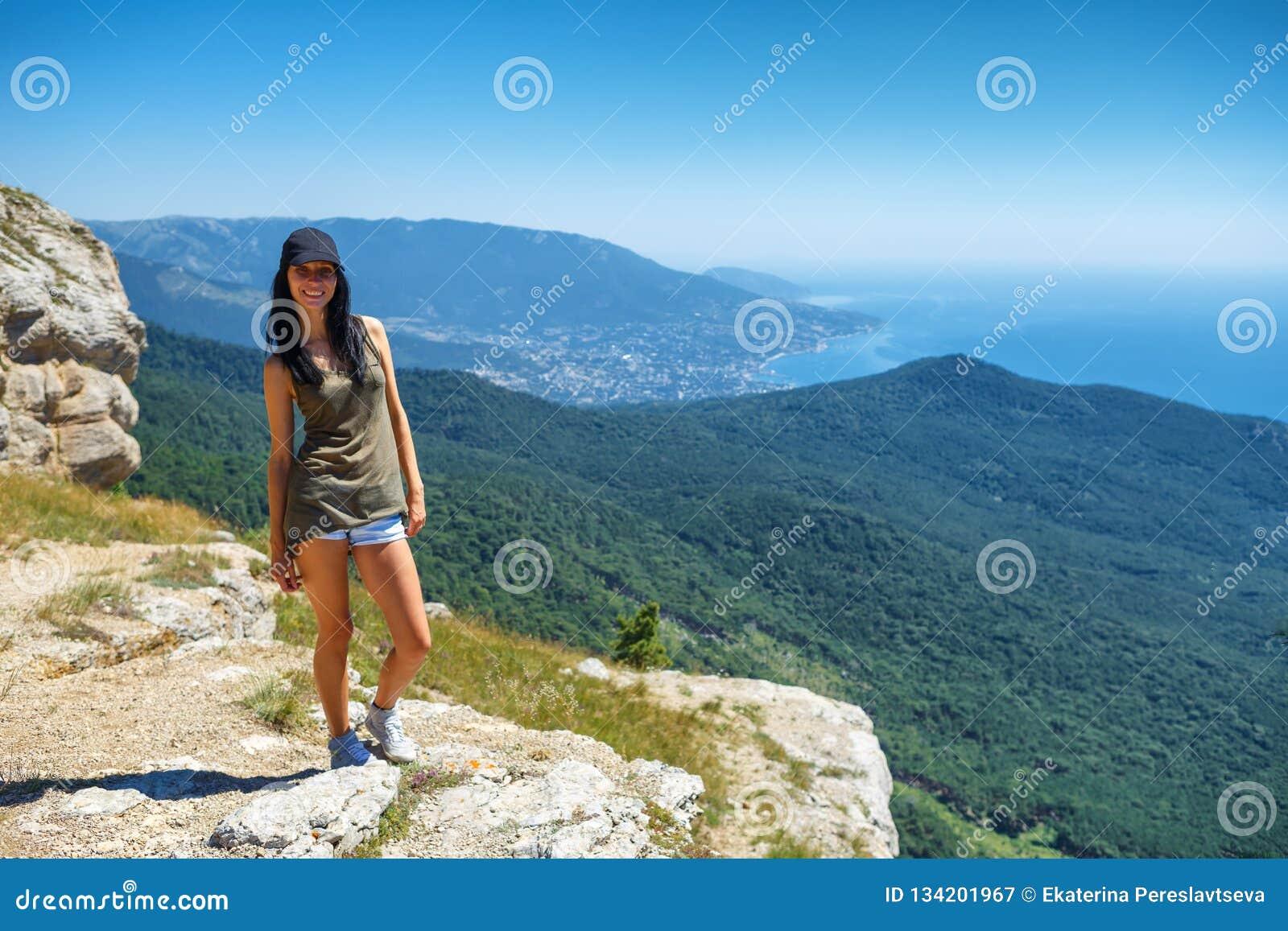 Красивая женщина в шортах стоя на скале с красивым видом, концепцией туризма и перемещением