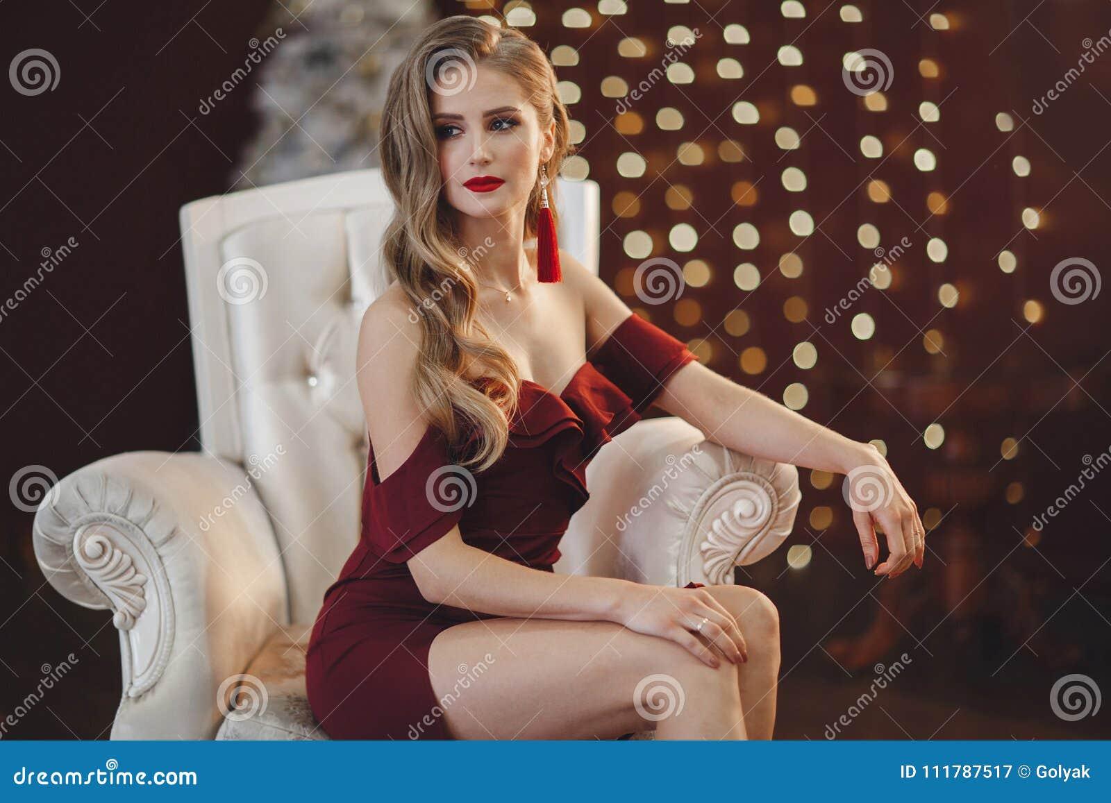 Красивая женщина в элегантном внешнем платье представляя самостоятельно, сидящ в стуле