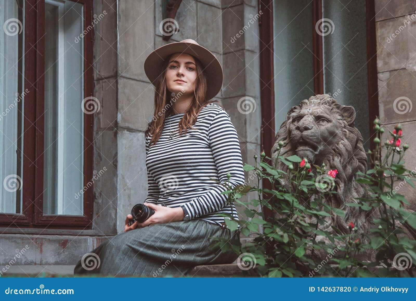 Красивая женщина в striped рубашке и шляпе Держит камеру около статуи льва на фоне старой