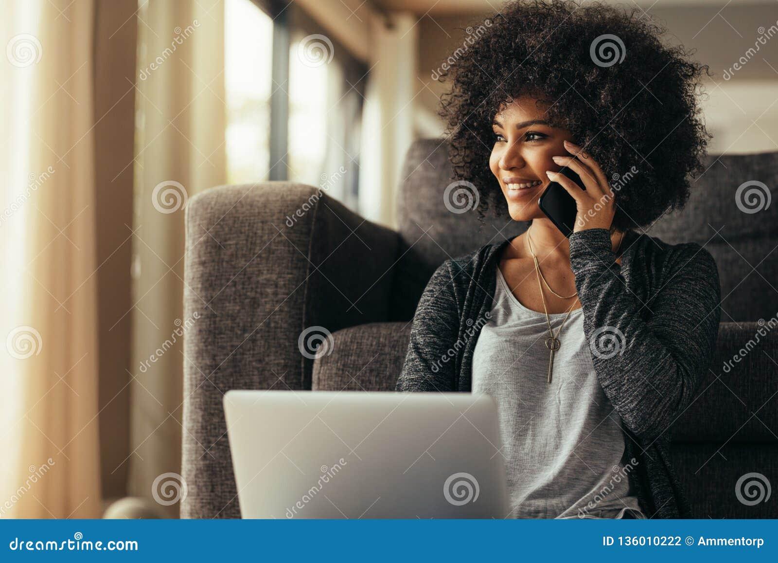 Красивая женщина дома с ноутбуком и говорить на сотовом телефоне