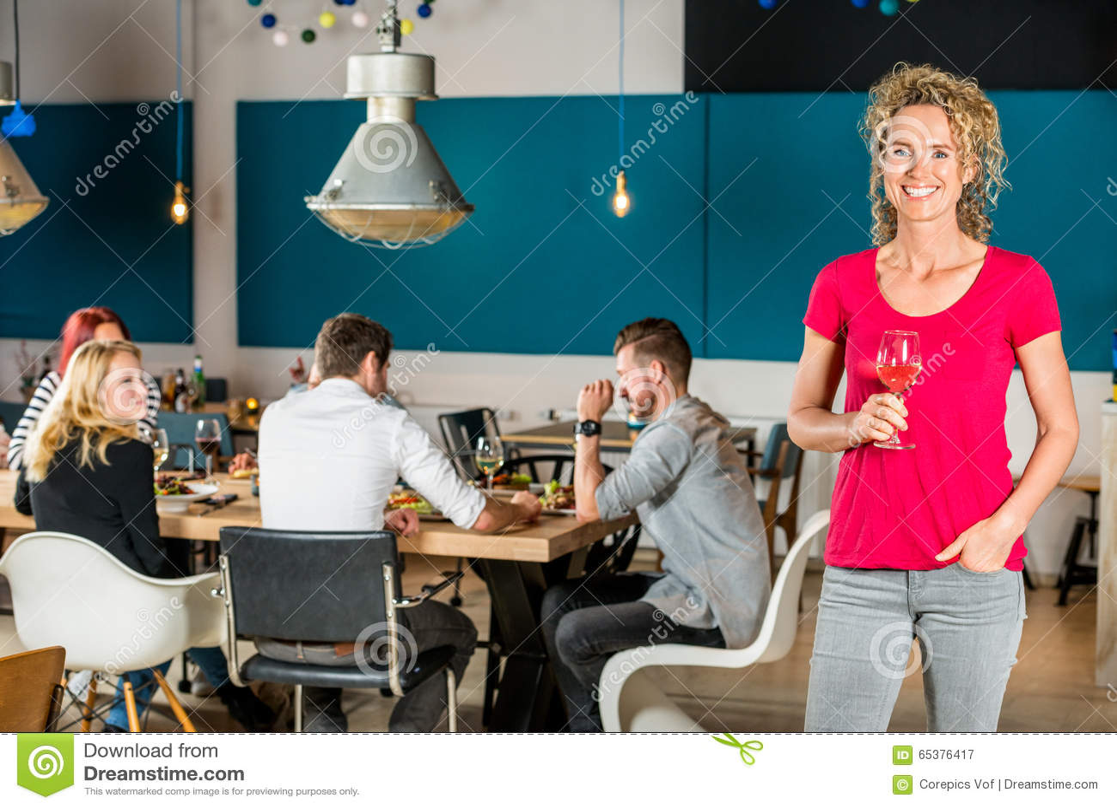 Красивая женщина держа рюмку на кафе