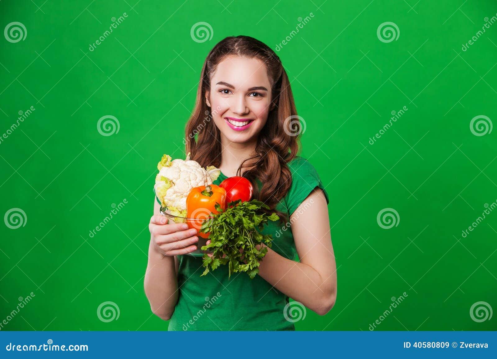 Красивая женщина держа свежую и здоровую еду На зеленой предпосылке