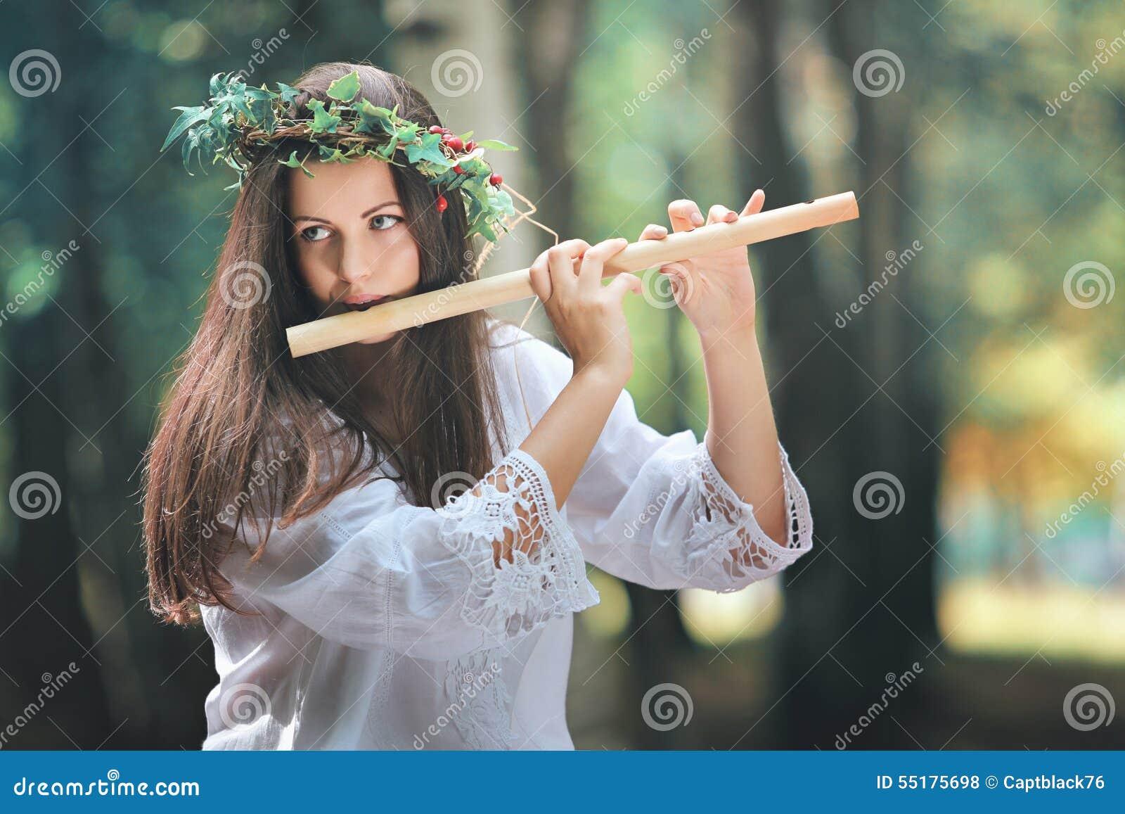 Красивая женщина играя каннелюру в лесе