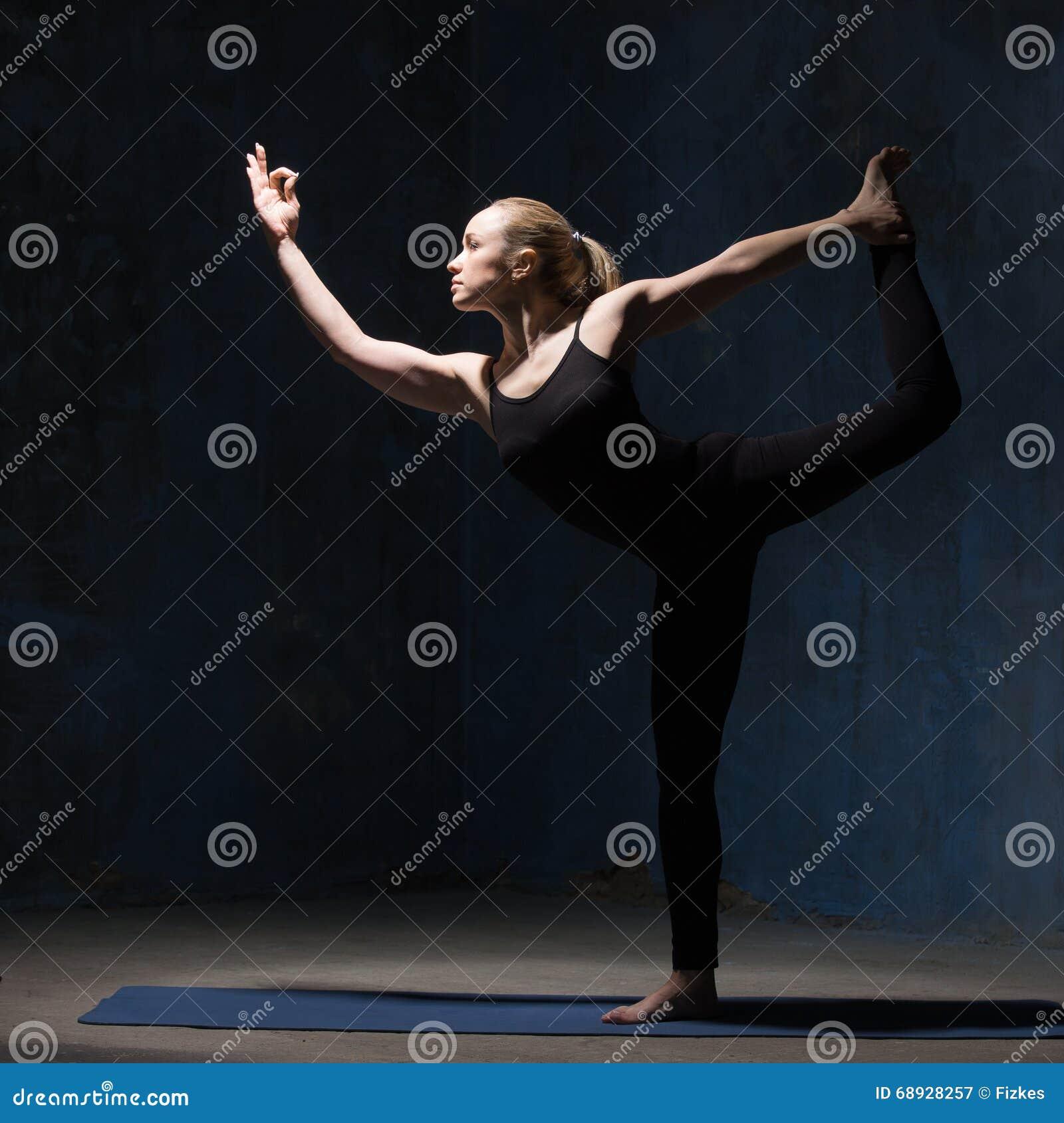 Красивая женщина йоги стоя в Natarajasana