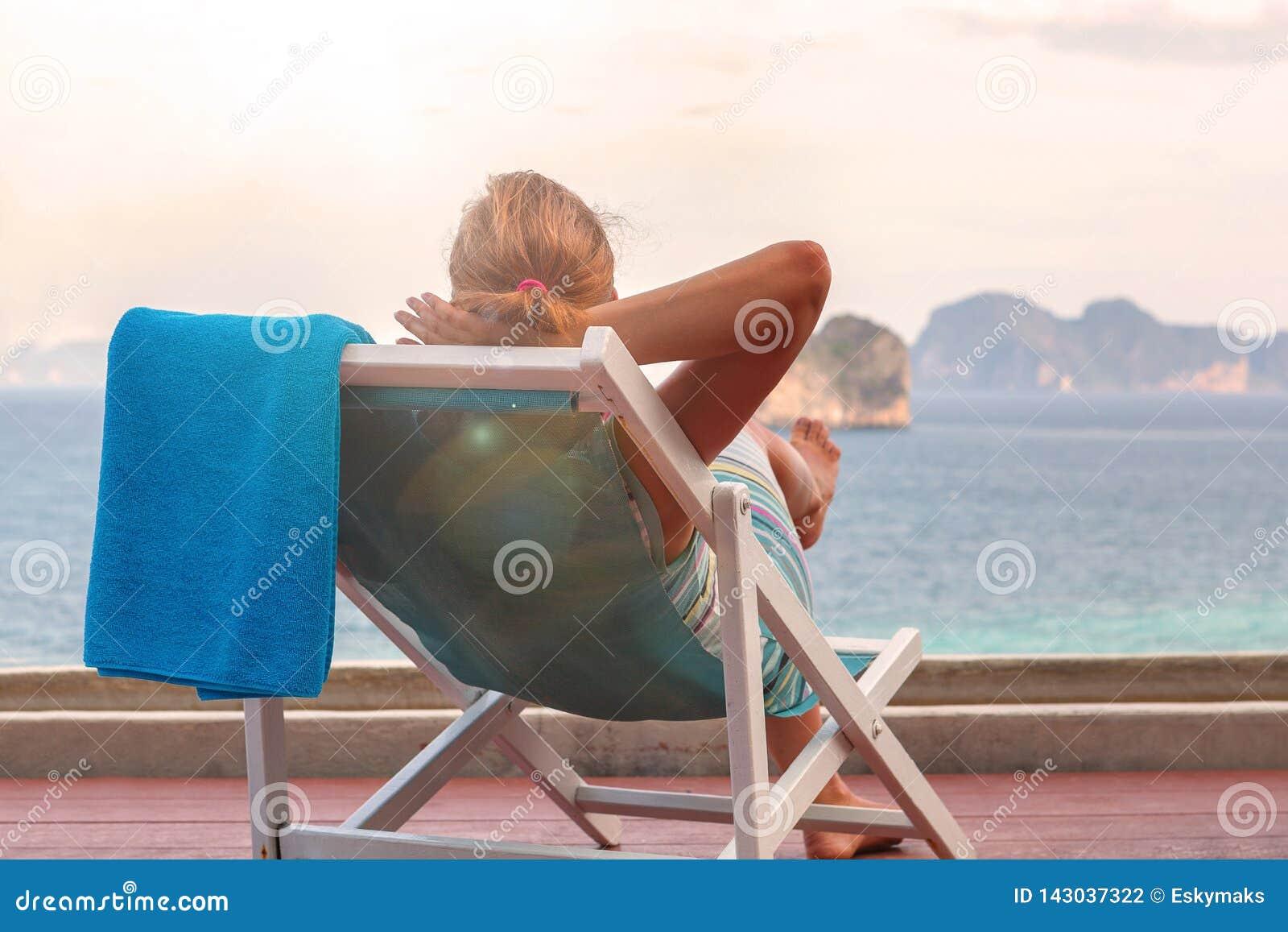Красивая женщина на океане террасы с видом на заходе солнца
