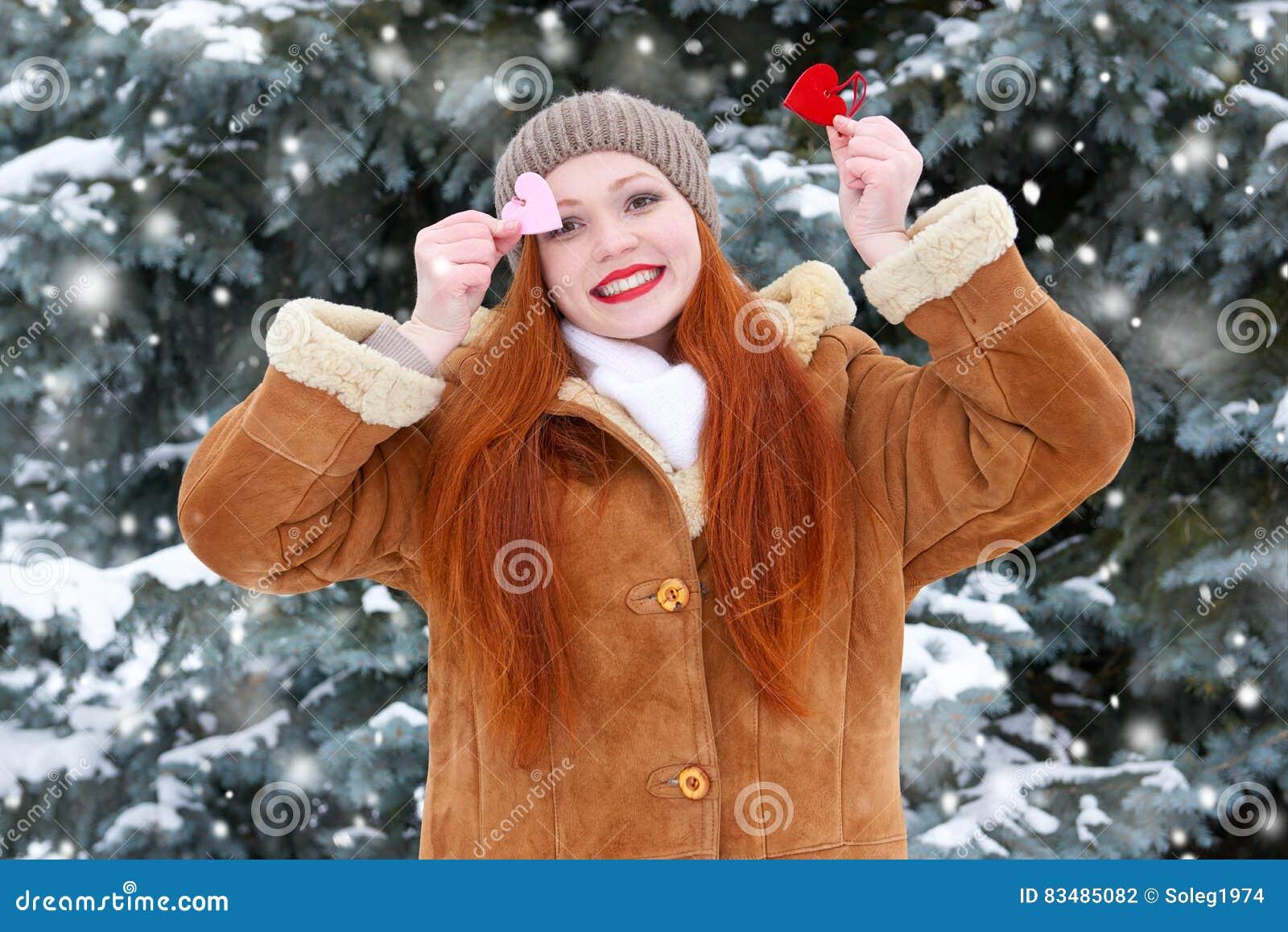 Красивая женщина на представлять зимы внешний с формой сердца забавляется, концепция праздника, снежные ели в лесе, длинных красн