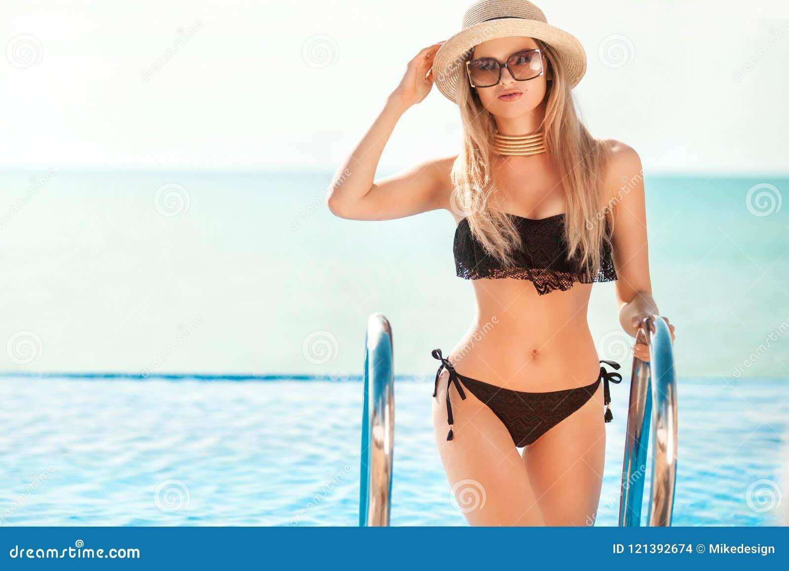 Красивая женщина пригонки в черном костюме и шляпе заплыва представляя на пляже каникула территории лета katya krasnodar