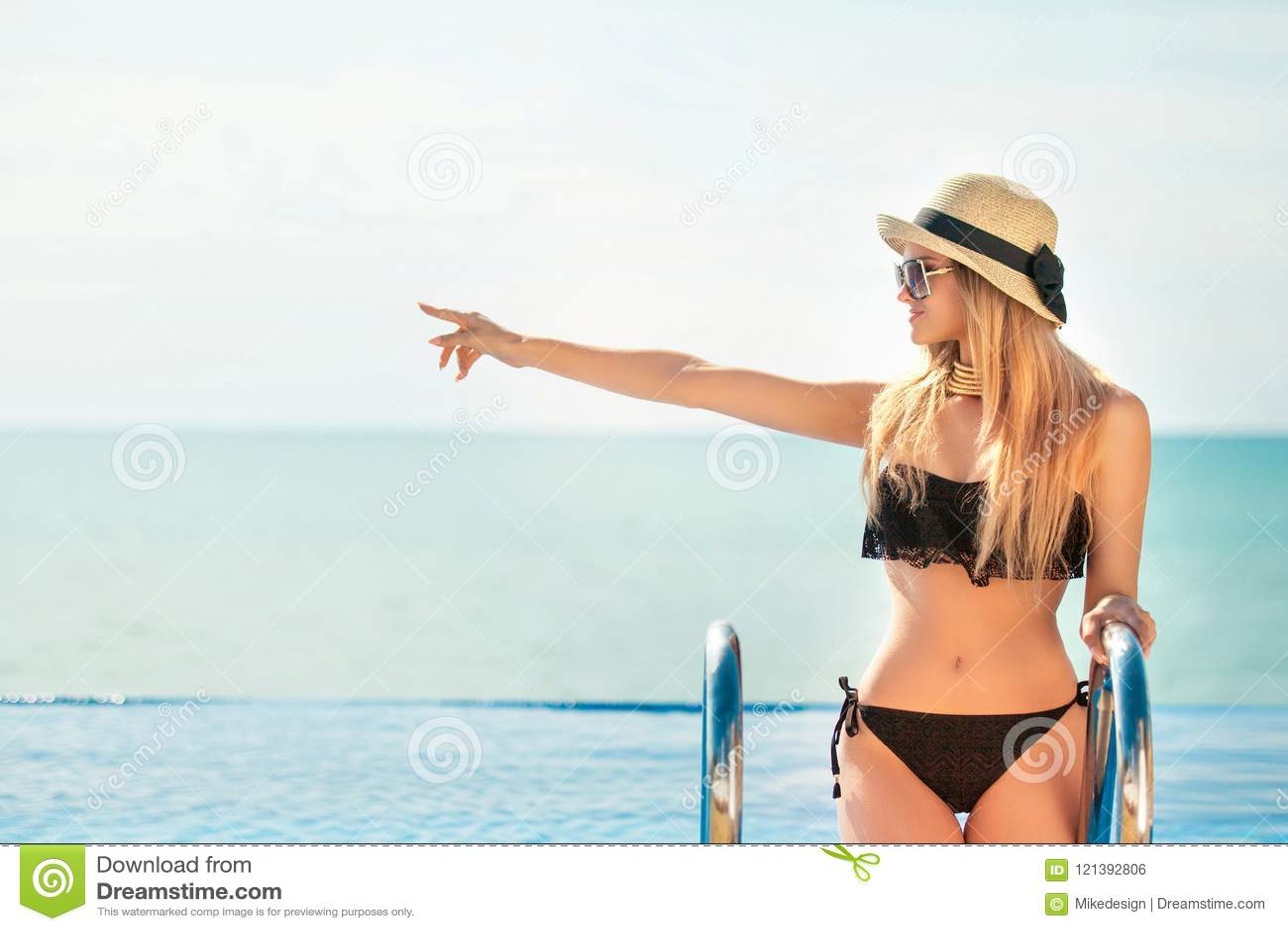 Красивая женщина пригонки в черном костюме и шляпе заплыва представляя на пляже каникула территории лета katya krasnodar Модельны
