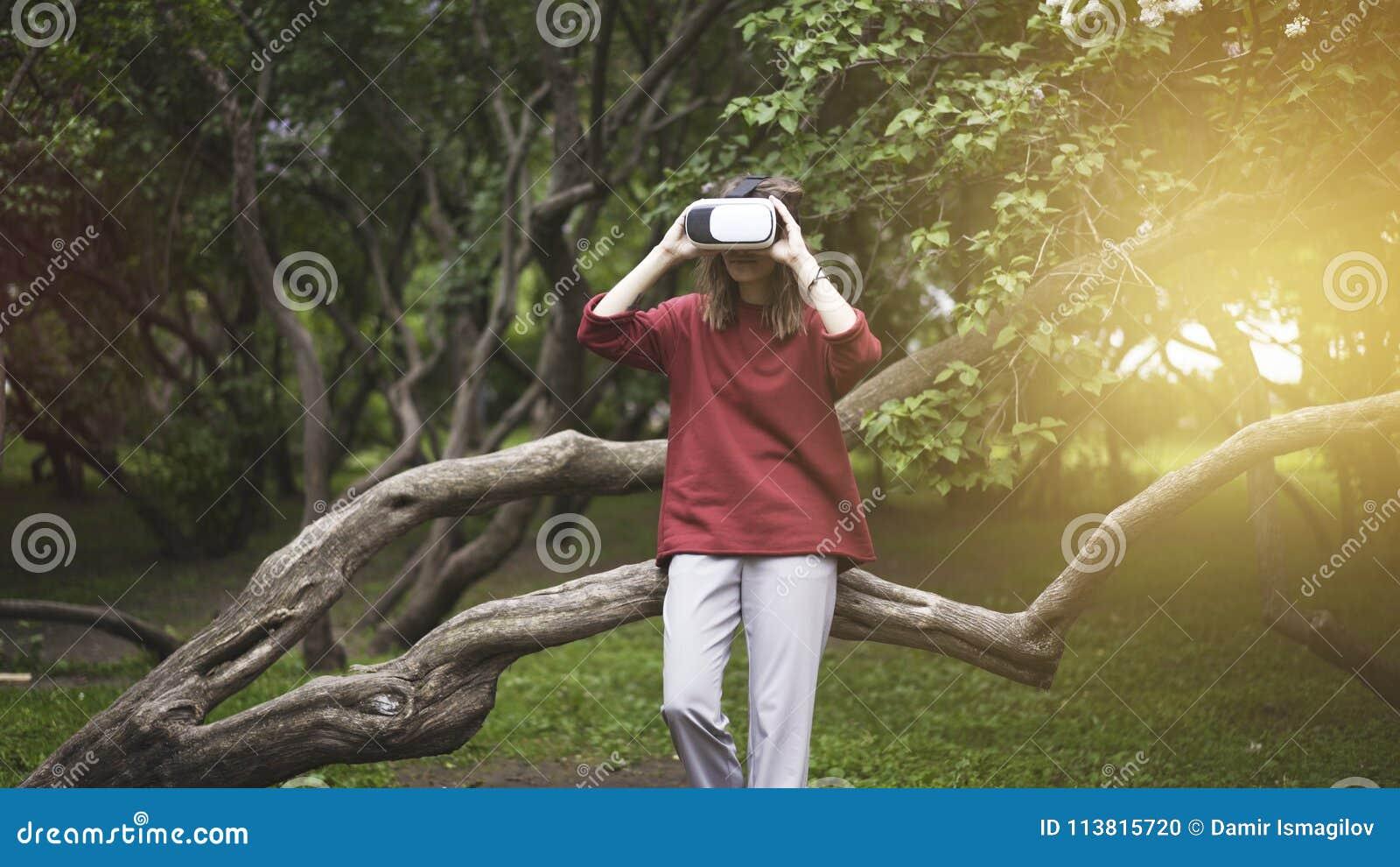 Красивая женщина при виртуальная реальность сидя на стволе дерева в внешнем парке Прибор стекел шлемофона VR зеленая природа ланд