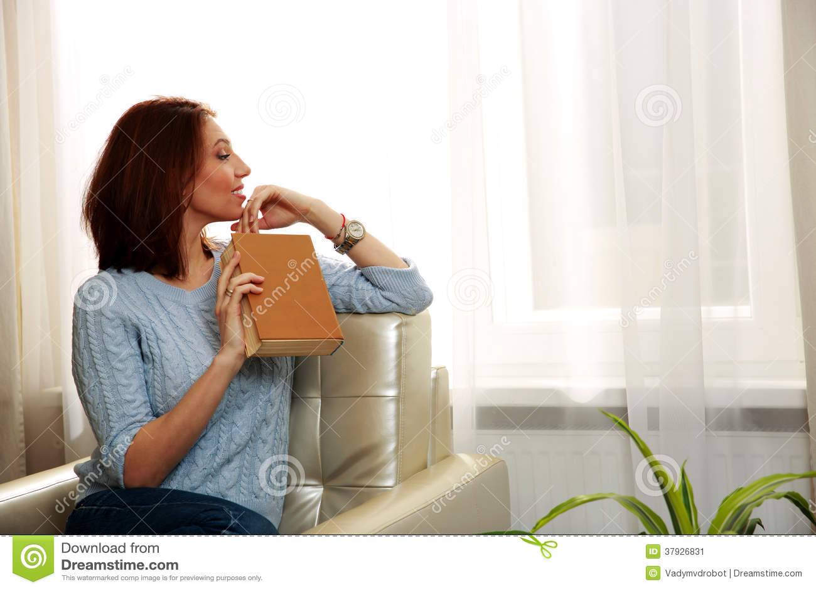 Красивая женщина сидя на софе и держа книгу