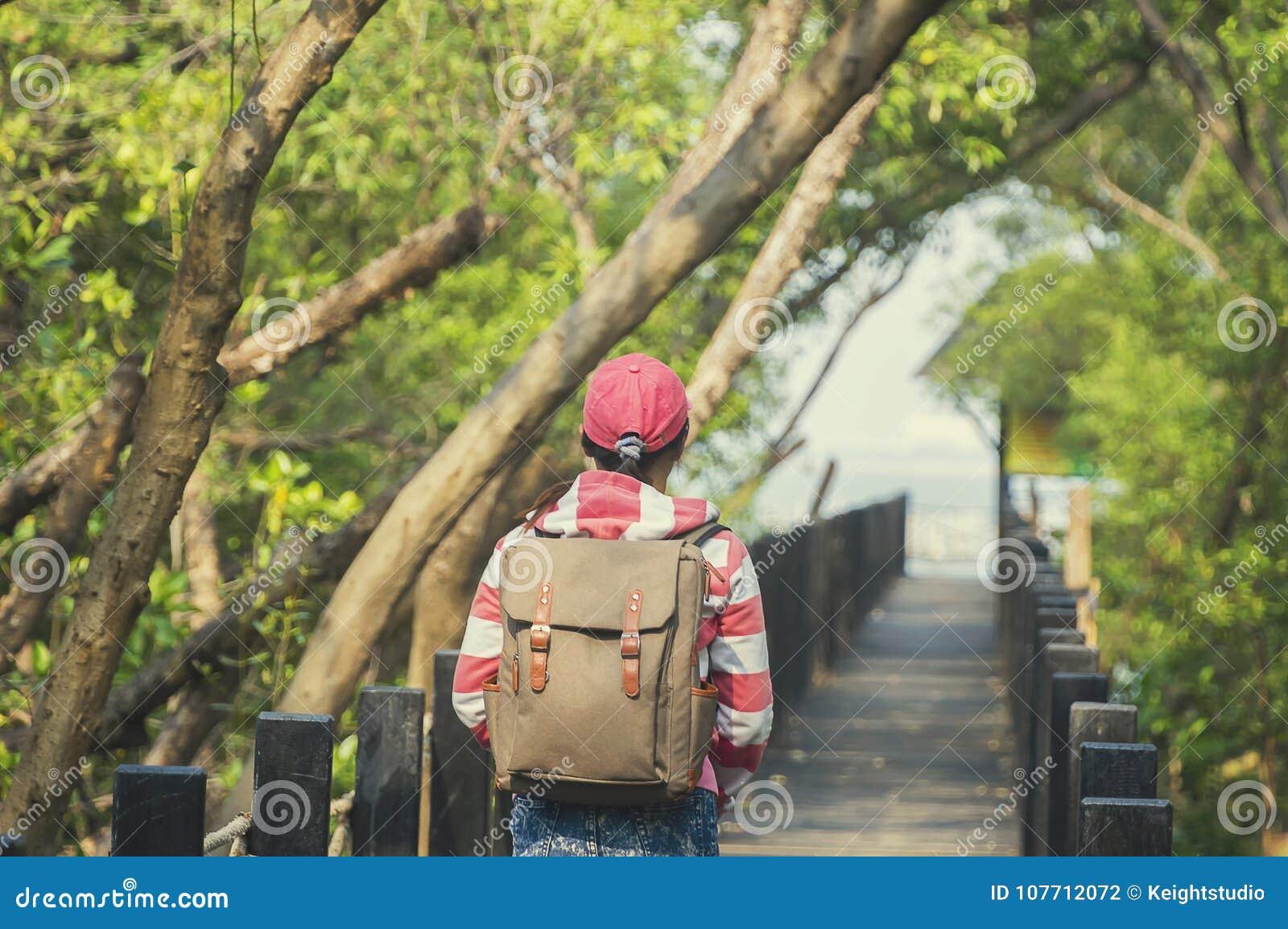 Красивая женщина студента работая на мосте смотря mang