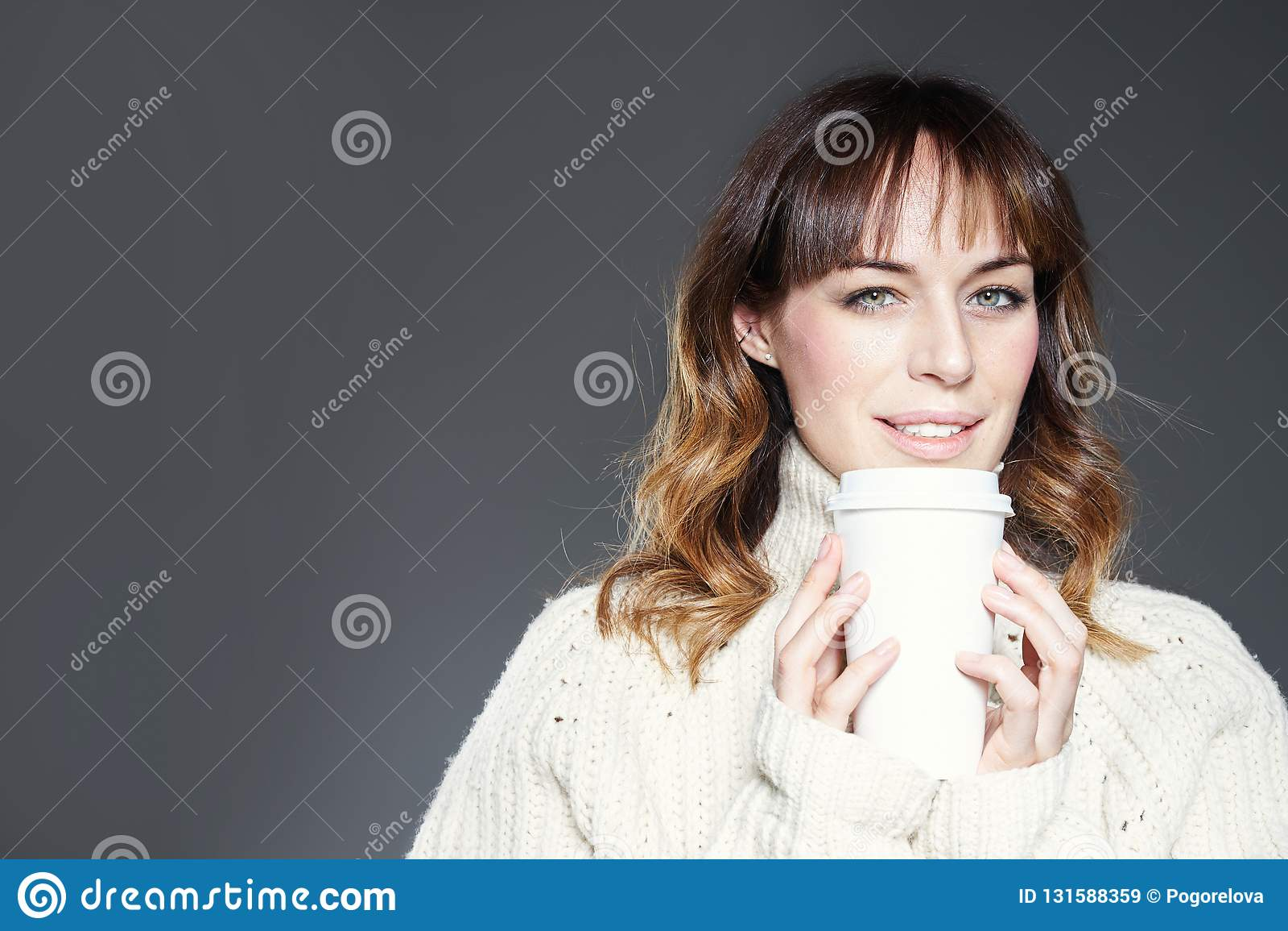 Красивая женщина с длинными волосами нося красные владения шляпы и свитера показывает бумажную устранимую кофейную чашку Космос д