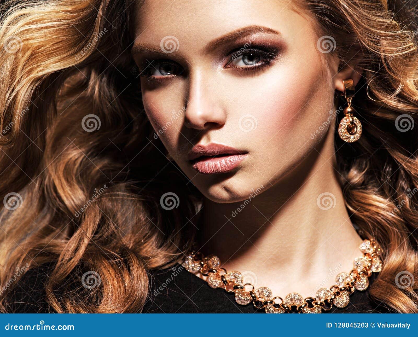 Красивая женщина с длинными ювелирными изделиями вьющиеся волосы и золота