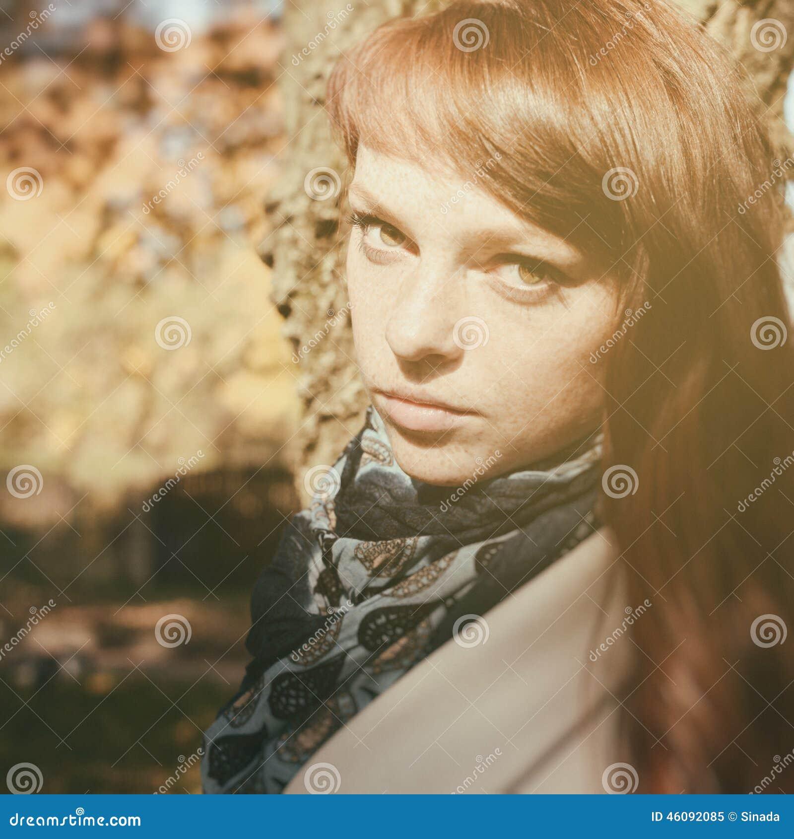 Красивая женщина с красными волосами в парке осени