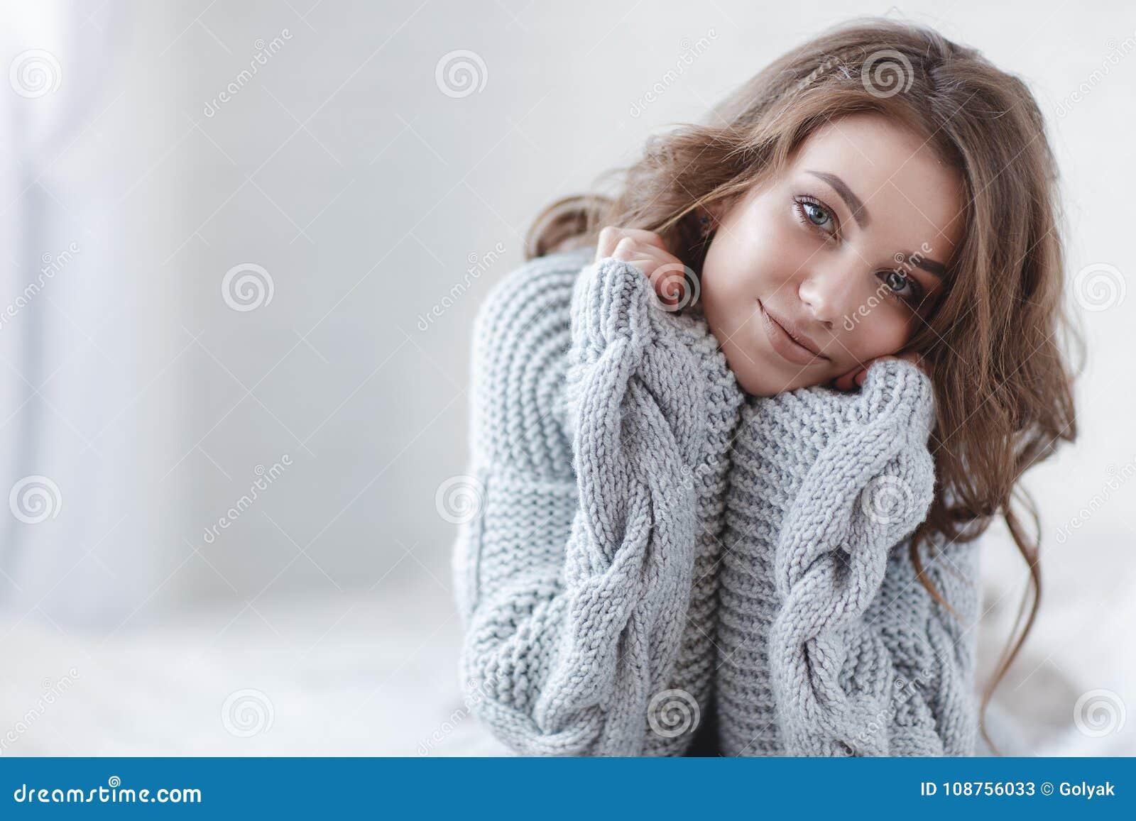 Красивая женщина с светлыми волосами в сером цвете связала свитер в яркой спальне на серой предпосылке