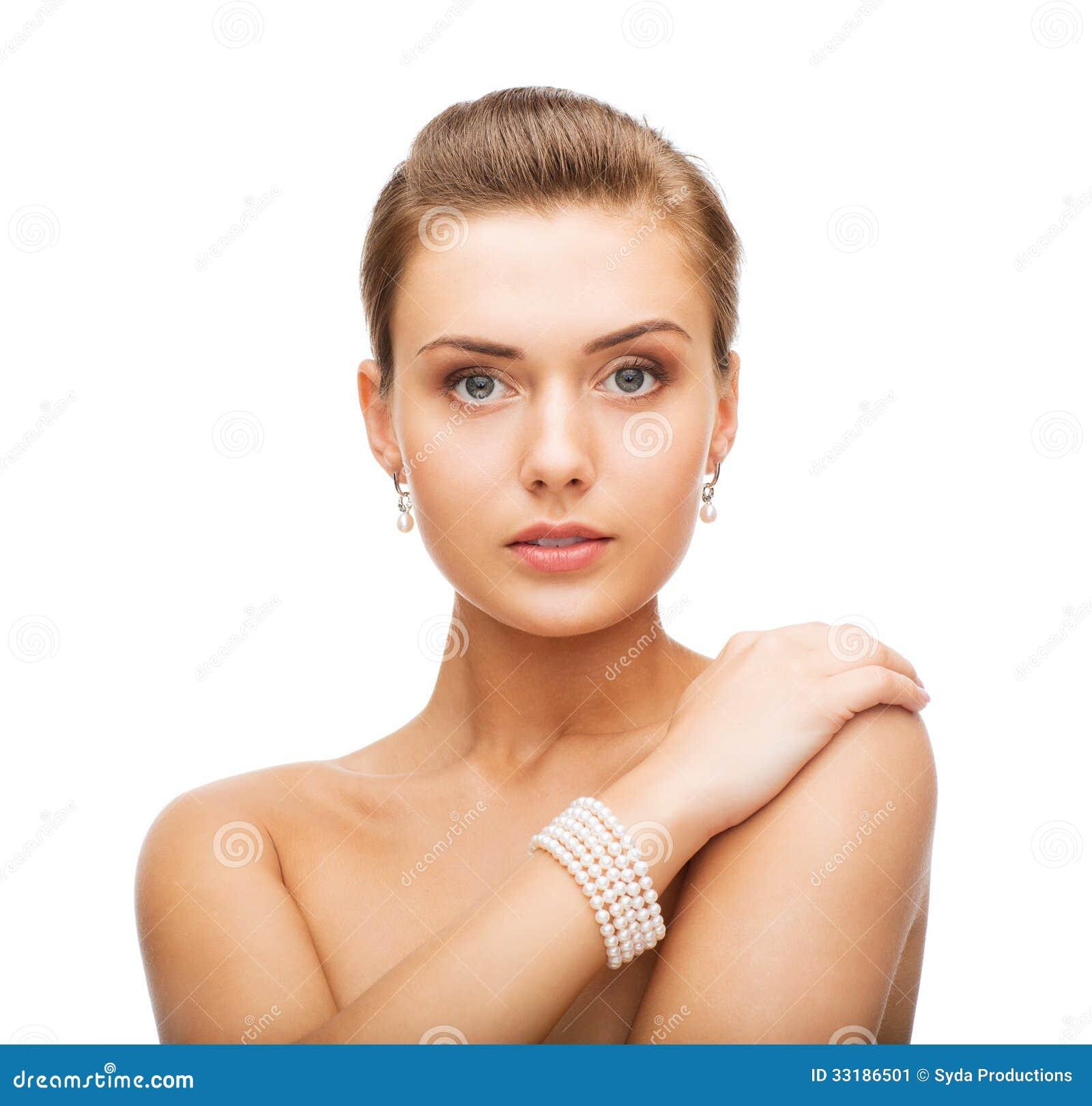 Красивая женщина с серьгами и браслетом жемчуга