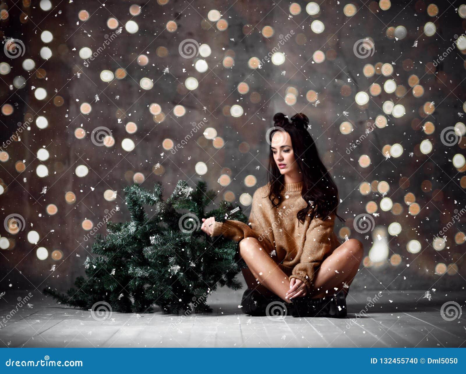 Красивая женщина хипстера с елью и светами рождества в сексуальной связанной блузке свитера