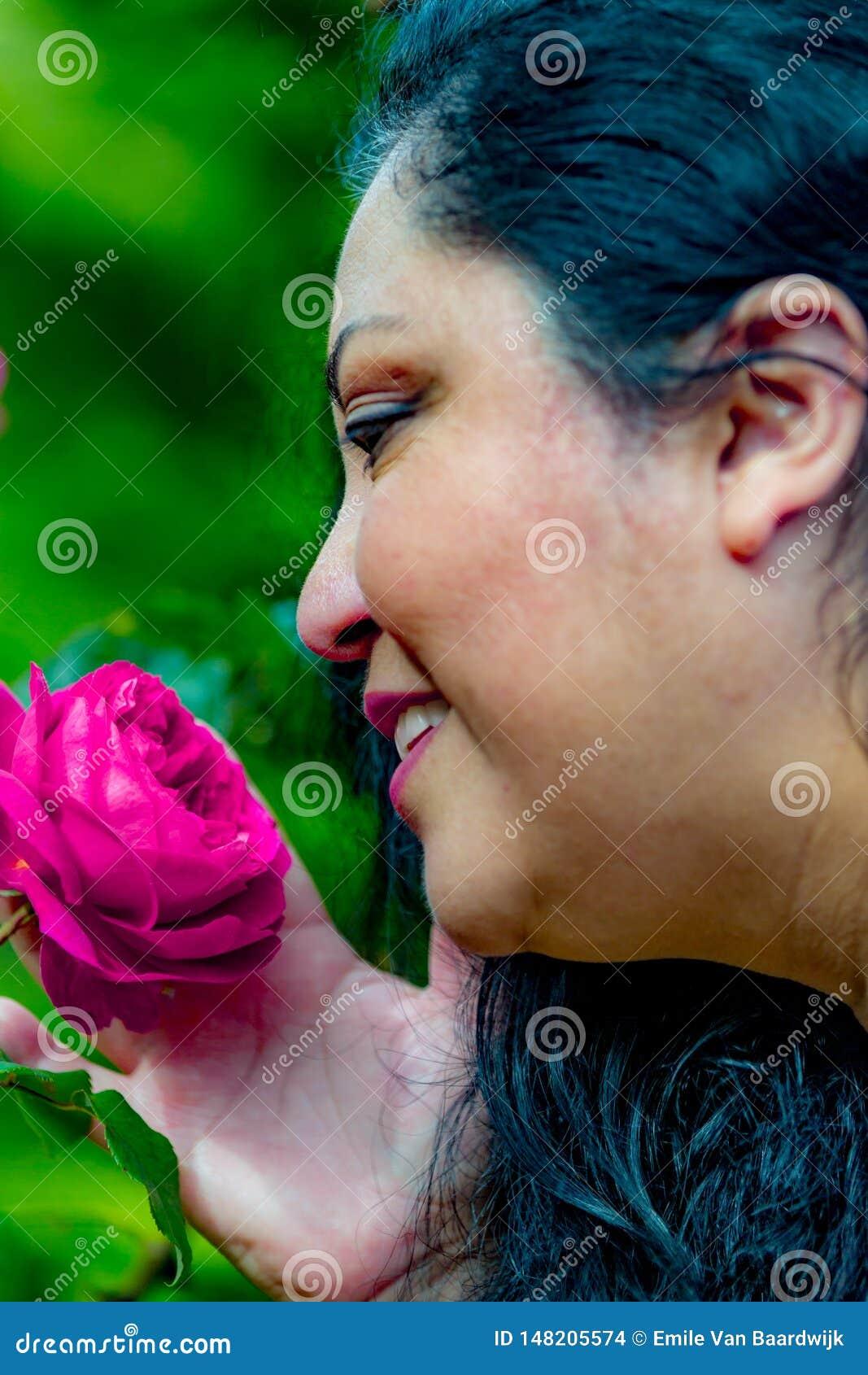 Красивая женщина latina с черными волосами наслаждаясь взглядом и запахом пинка