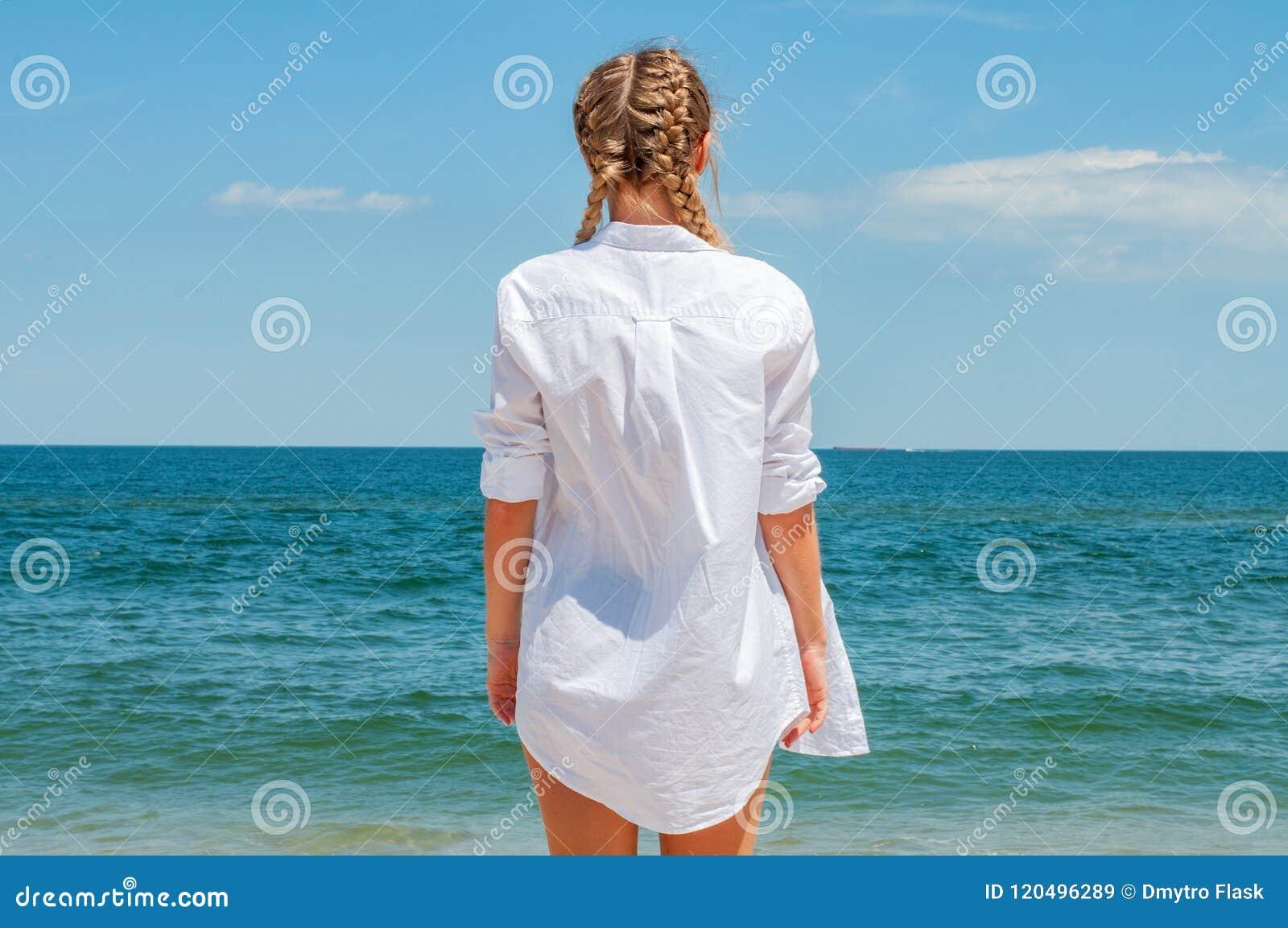 Красивая загоренная женщина в белой рубашке смотря океан, на пляже