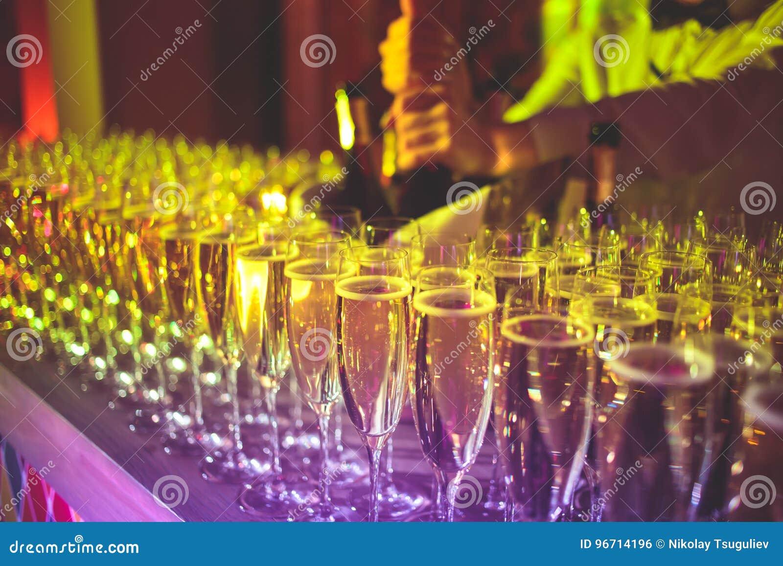 Красивая линия различных покрашенных коктеилей, текила, Мартини, водочки, и других спирта на украшенной поставляя еду таблице бан