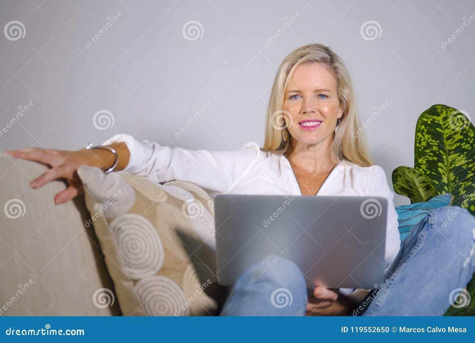 Красивая и счастливая элегантная белокурая женщина предыдущее 40s ослабила дома живущую комнату используя интернет на comfortabl